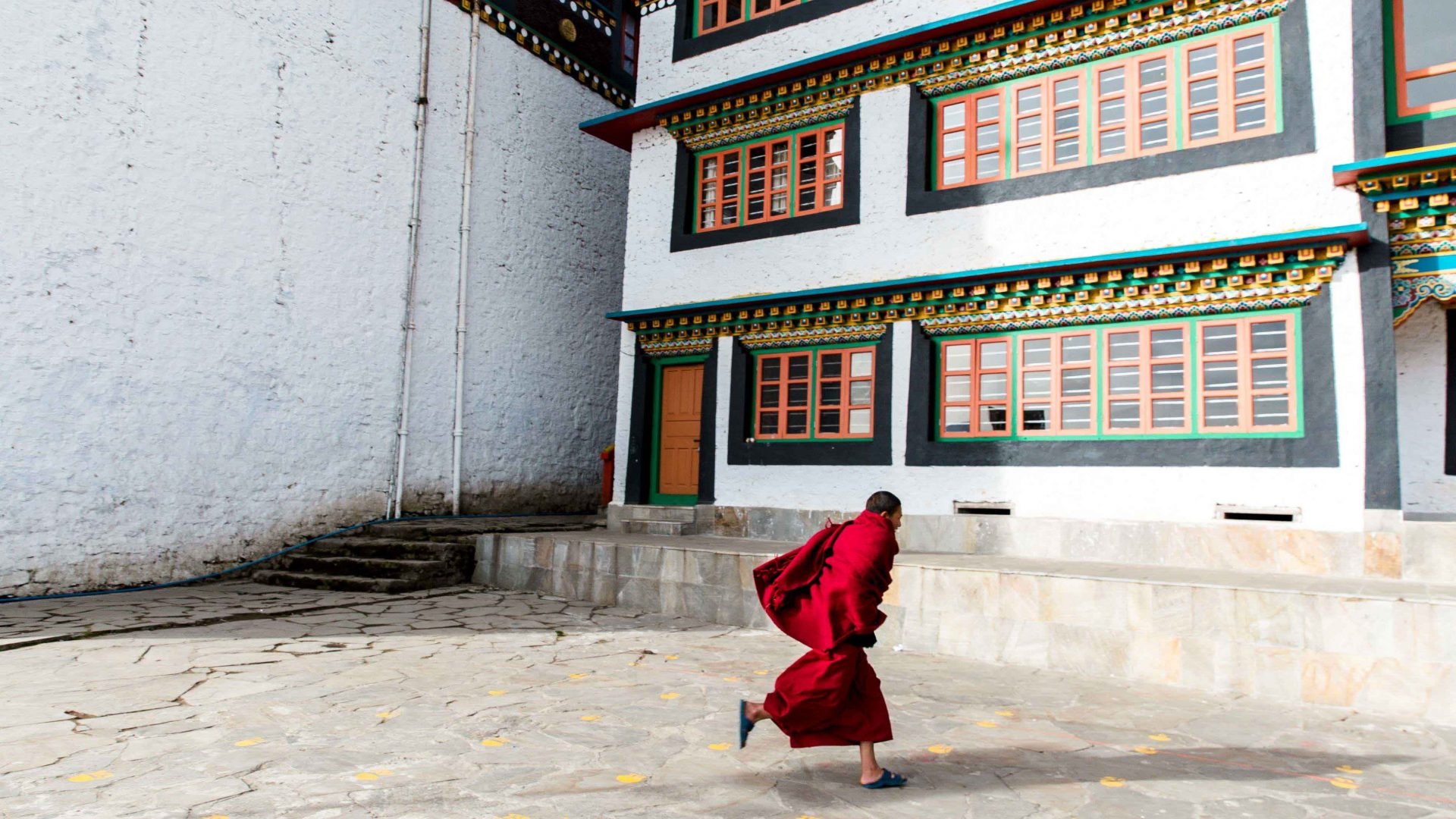 A young monk runs to morning prayer class at the Tawang Monastery, Arunachal Pradesh, India.