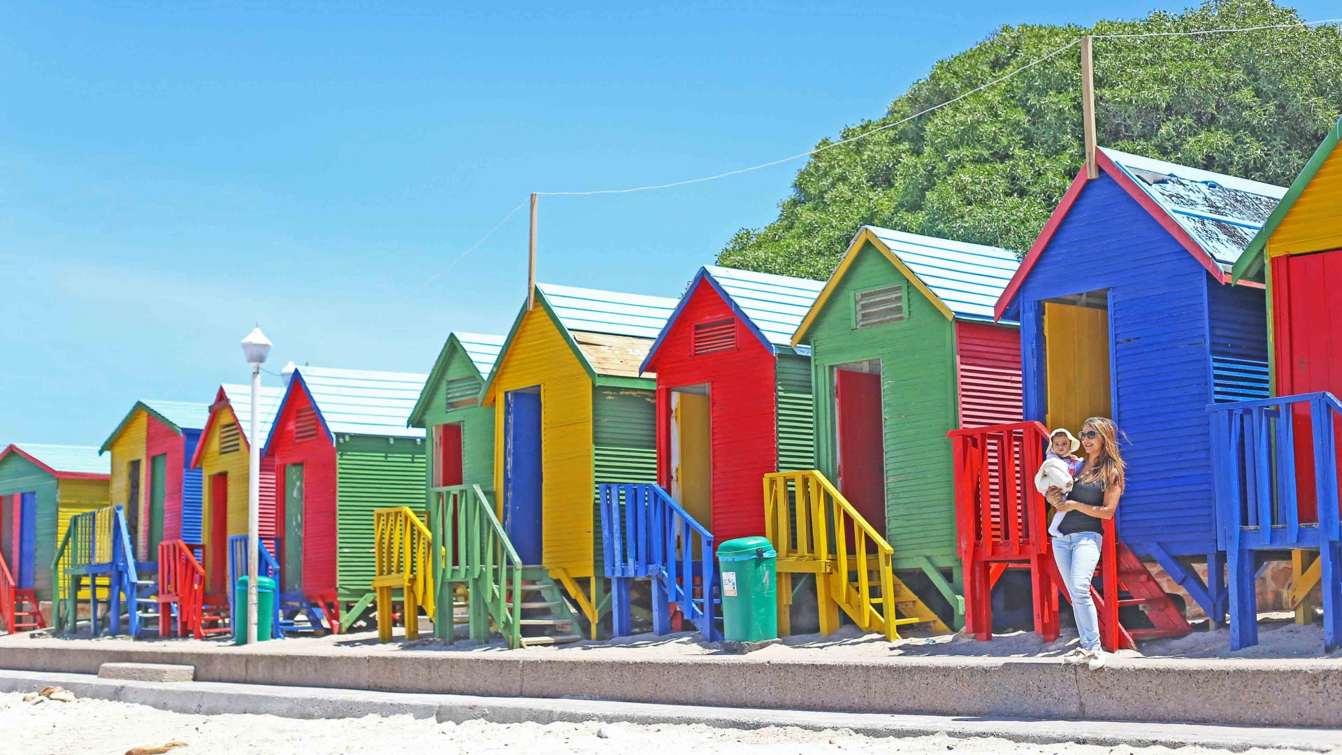 Baby Gia Sereni and her mother, writer Anashi Shah, outside these colorful beach huts in South Africa.