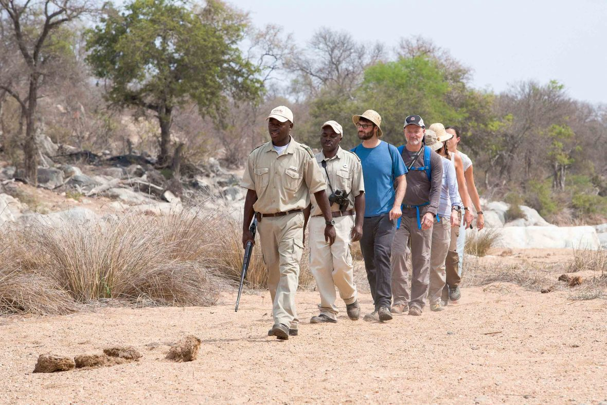 Lodge guests walk along the dry Mohlabetsi riverbed in Balule Nature Reserve in South Africa.