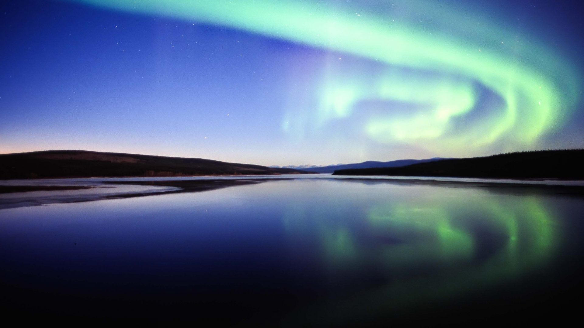 The northern lights shine brightly over a lake in the Yukon.