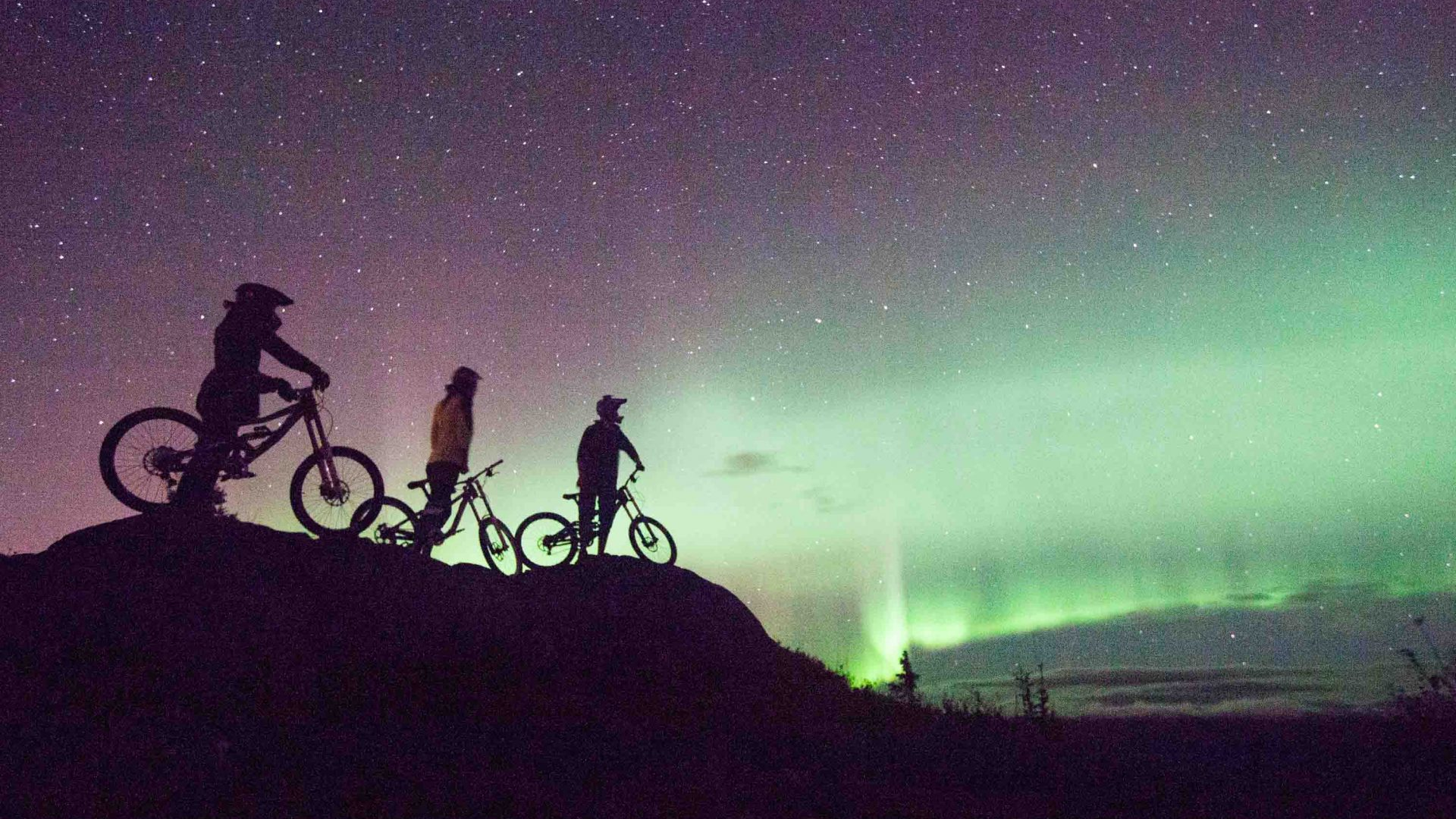 Mountain bikers enjoy the spectacle of the northern lights in the Yukon.