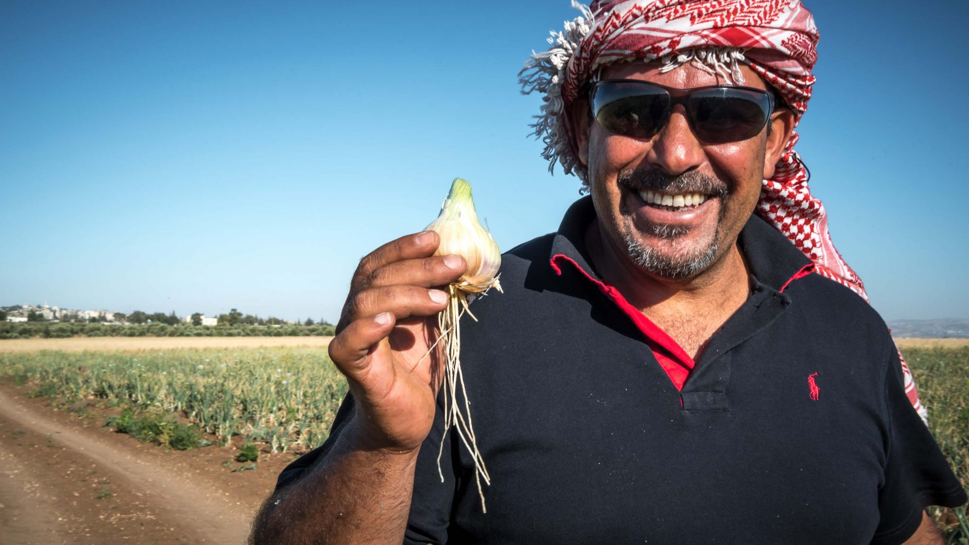 Guide Ahmed Al Omari shows off an onion bulb found while foraging around Umm Qais.