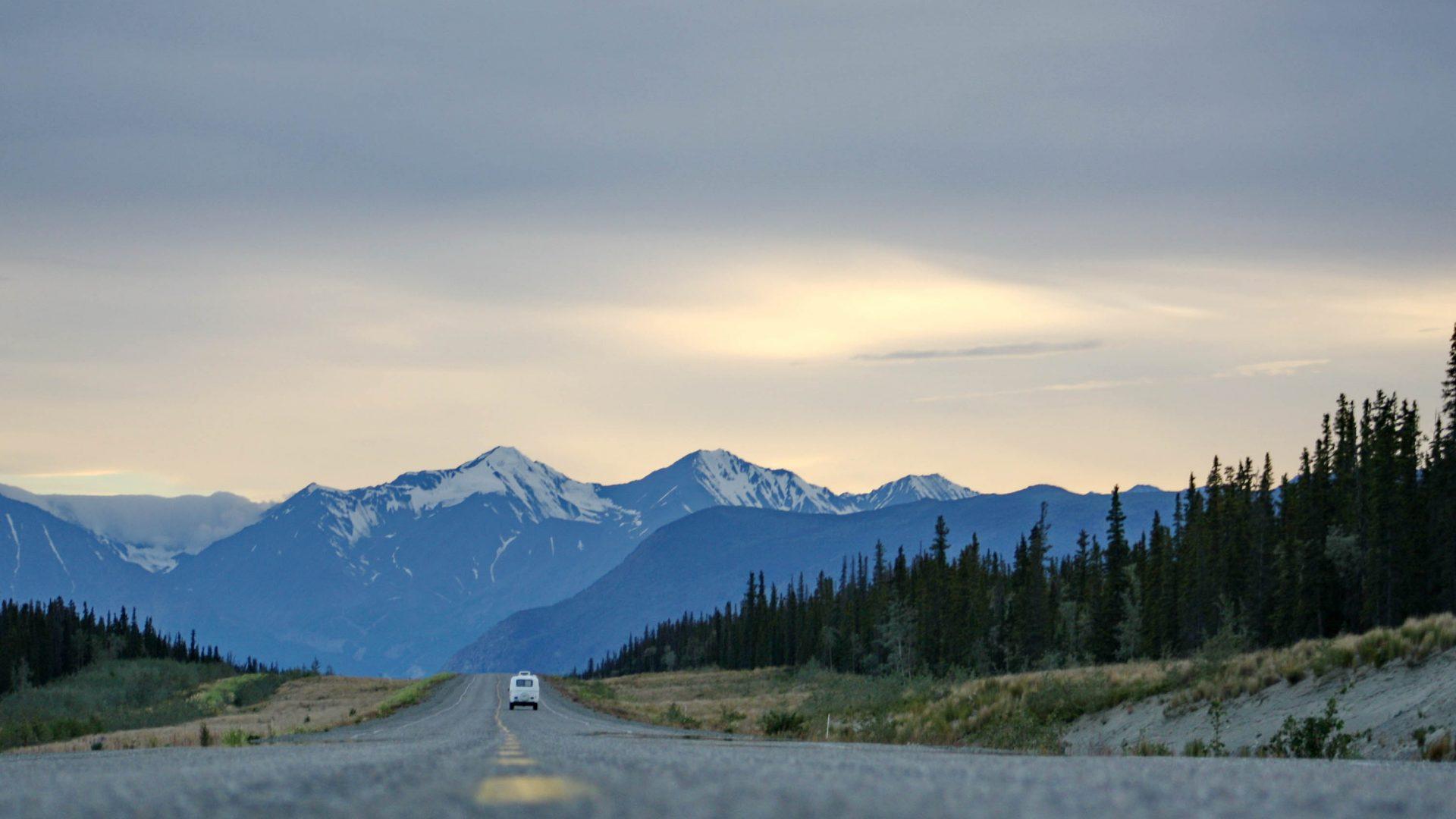 A van drives down the road in Alaska, USA.