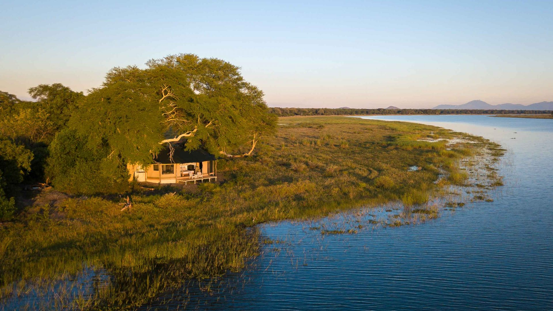 Accommodation sits on the river's edge at Kuthengo Camp in Liwonde National Park, Malawi.