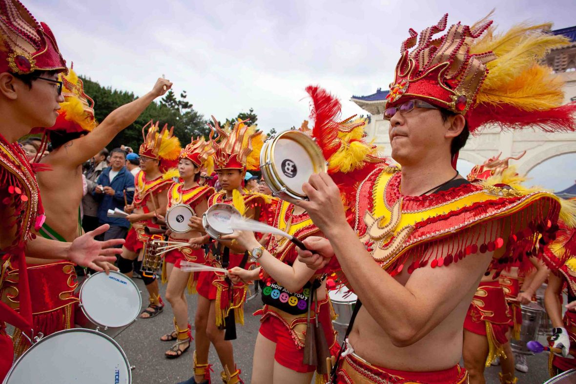 Men in brightly colored costumes revel in Taipei's Dream Parade.