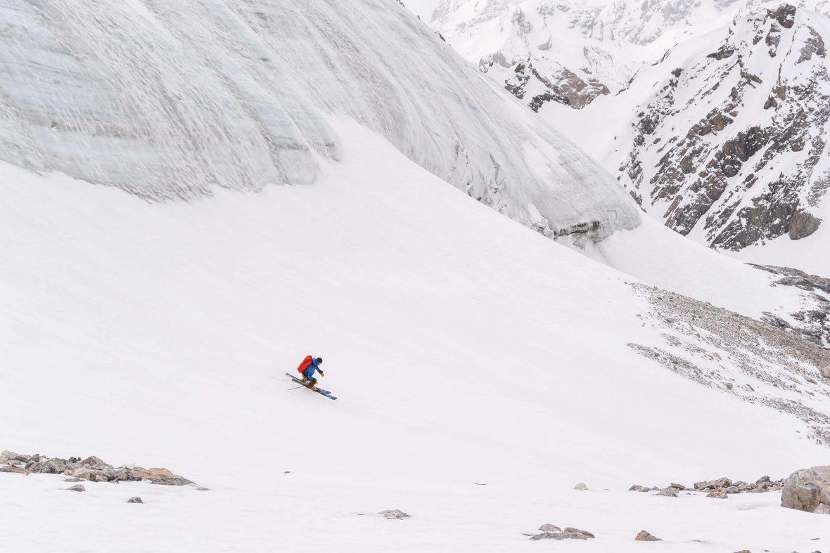 Huw Kingston's friend, Rich, skis past the snout of Zamok Glacier, Tajikistan.