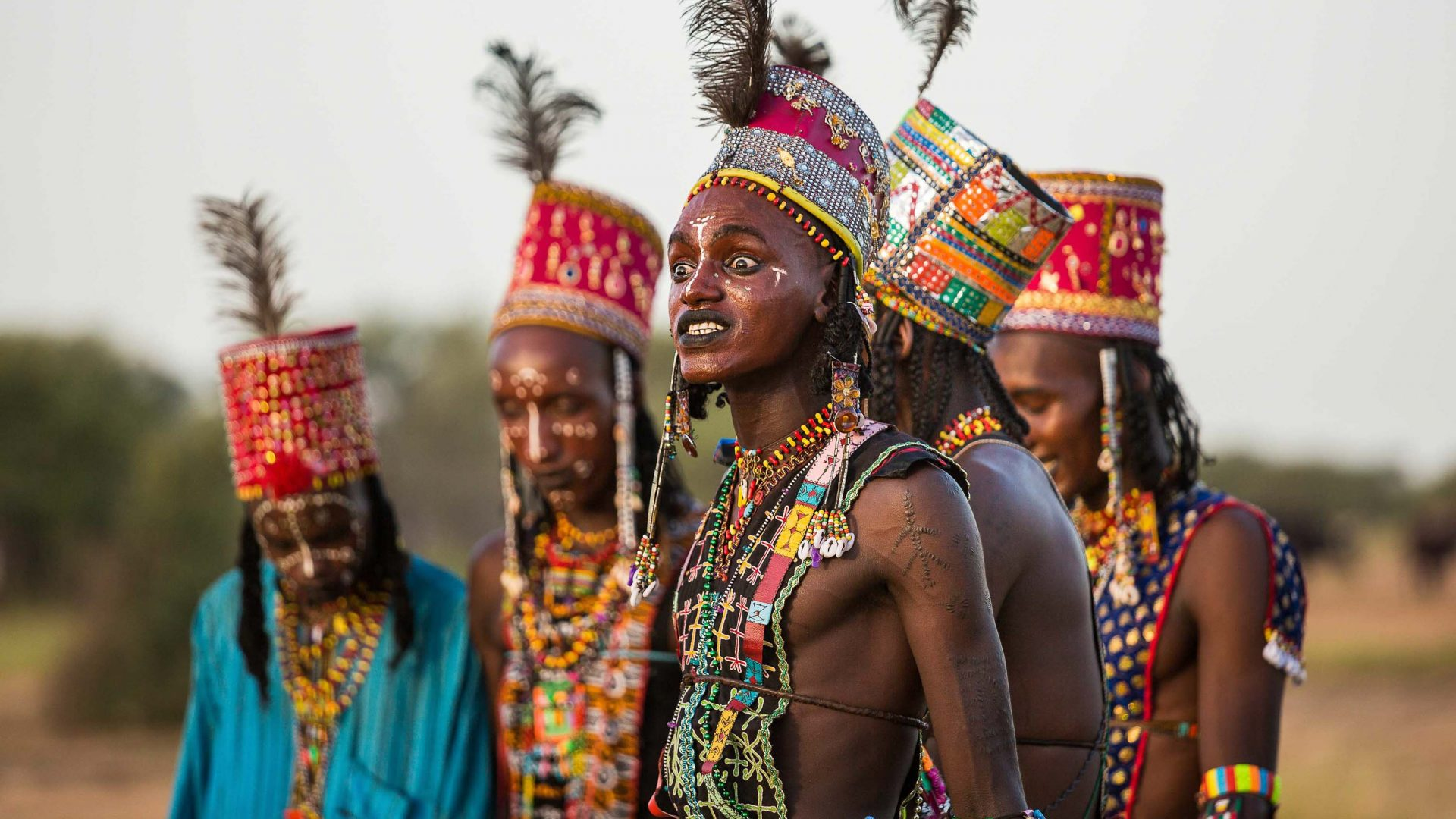 The Wodaabe men grimace during the dance to show off their white teeth. The ostrich feathers in their hats emphasizes their height.