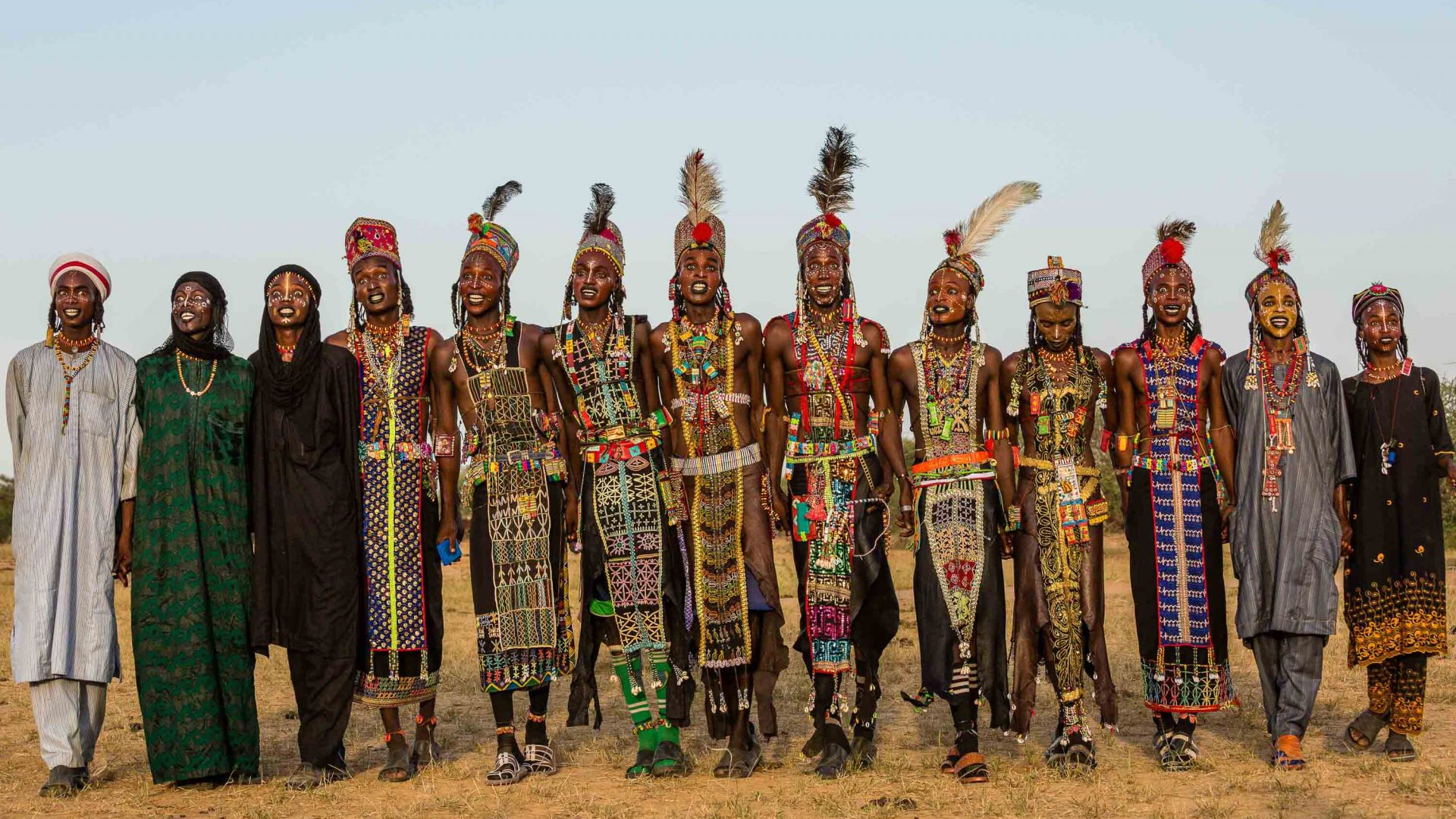 A long line of Wodaabe men and boys, wearing bejeweled leather tunics and sparkling crowns and feathers.