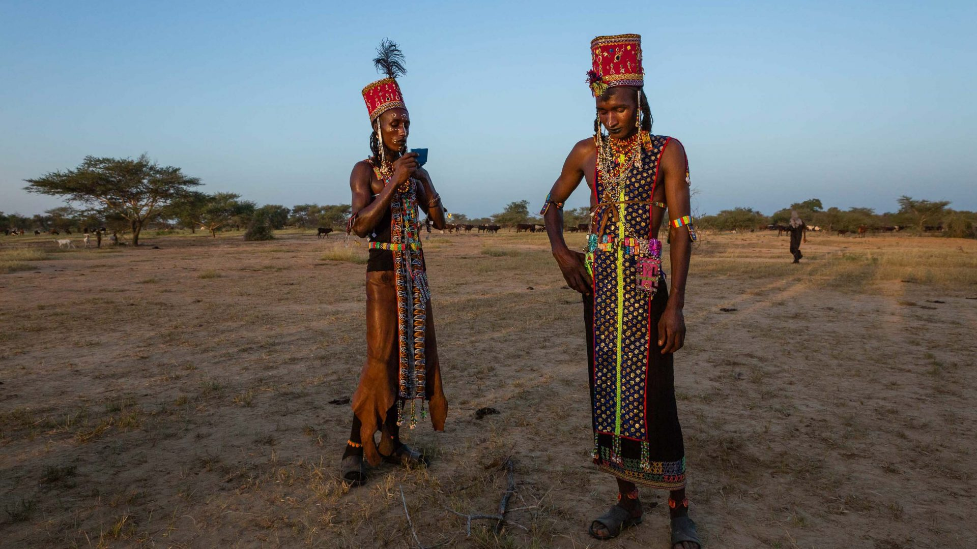 Two Wodaabe men take a break from dancing to catch their breath—the Gerewol festival is a grueling test of endurance for men.