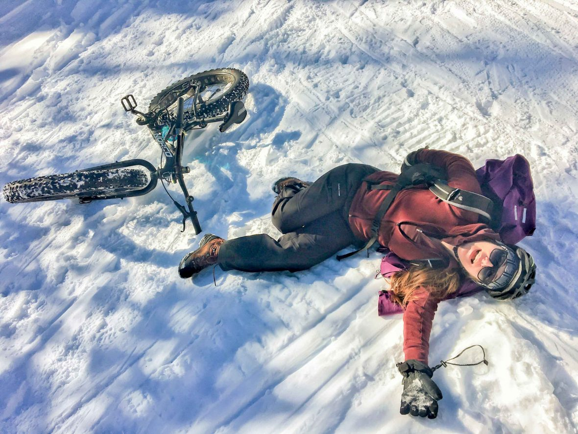 Writer Kristin Kent flat-out in the snow after coming off her bike in the Canadian Rockies.