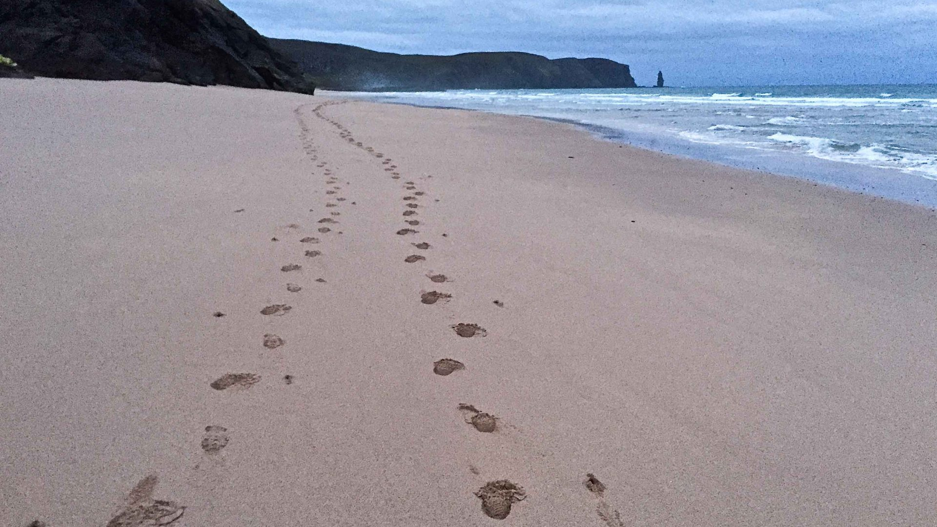 The first footsteps on lonely Sandwood Bay along the Cape Wrath Trail, Scotland.