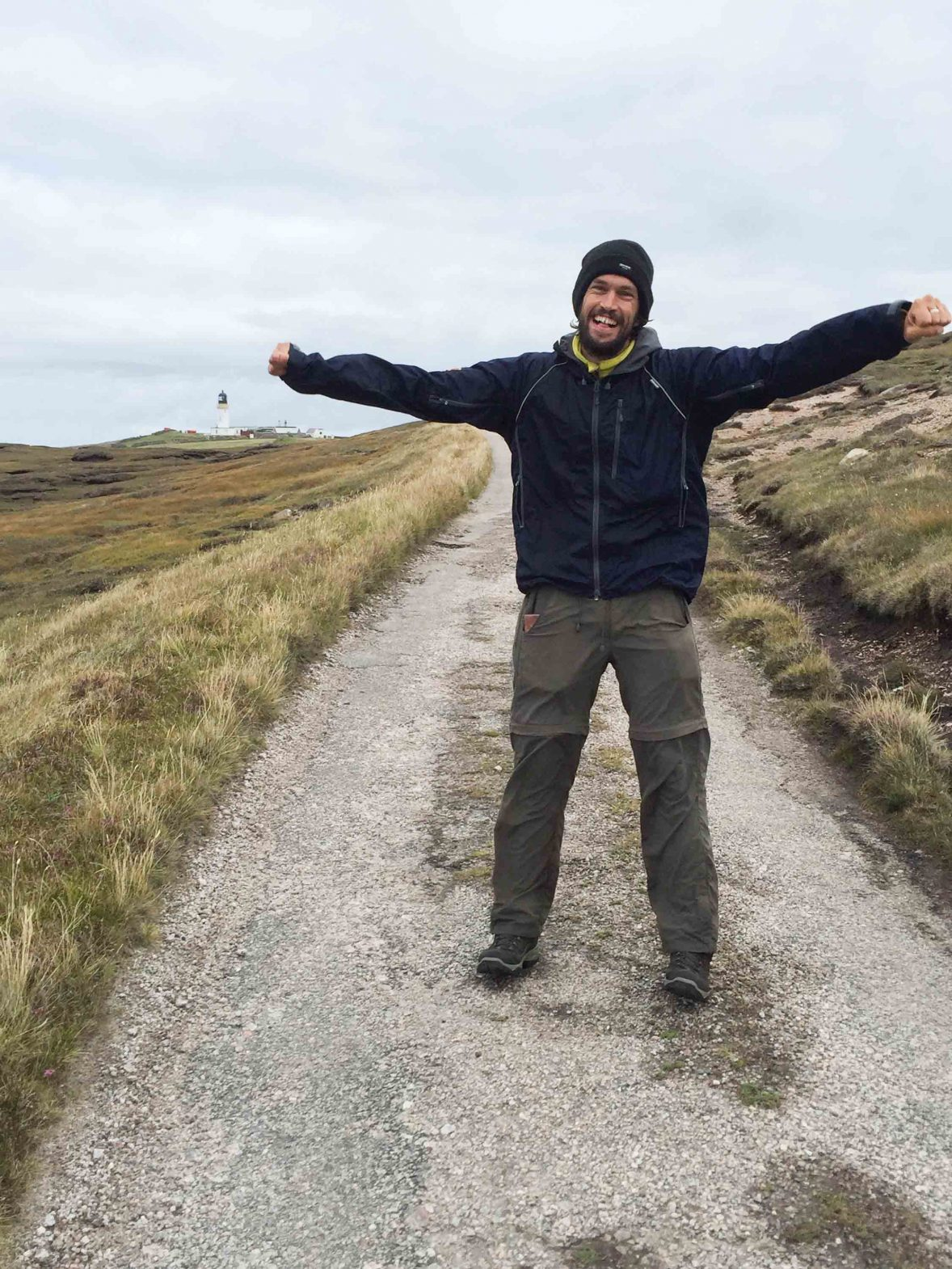 Writer Luke Waterson arriving at the end of the Cape Wrath Trail with Cape Wrath lighthouse in the background.