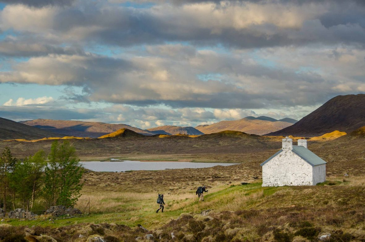 Hikers approach a mountain shelter in Cape Wrath, Scotland.