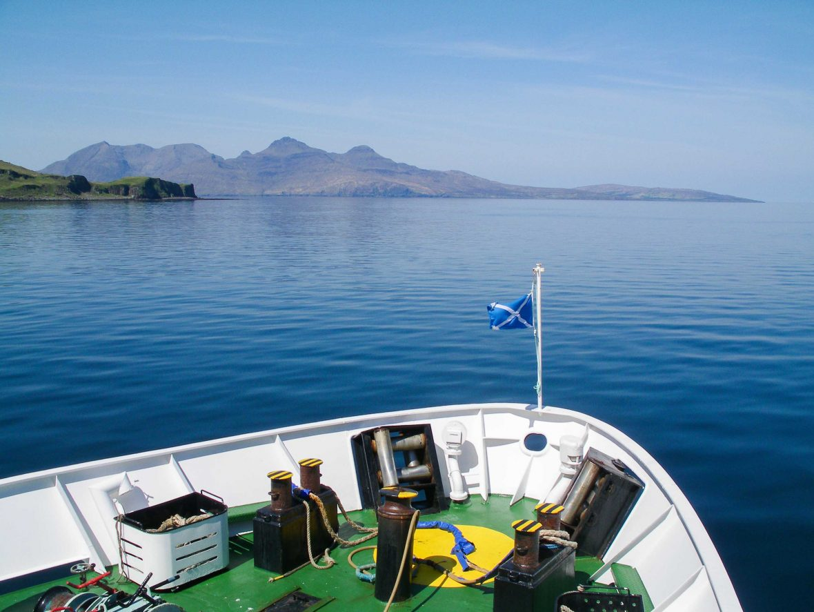 The Caledonian Macbrayne (Calmac) ferry makes its way toward Rum along the coast of Eigg, Scotland.