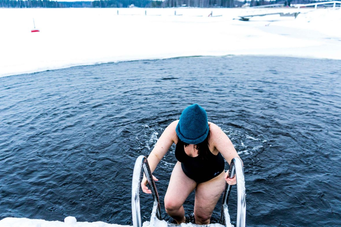 A woman in Finland exits the water after ice swimming.