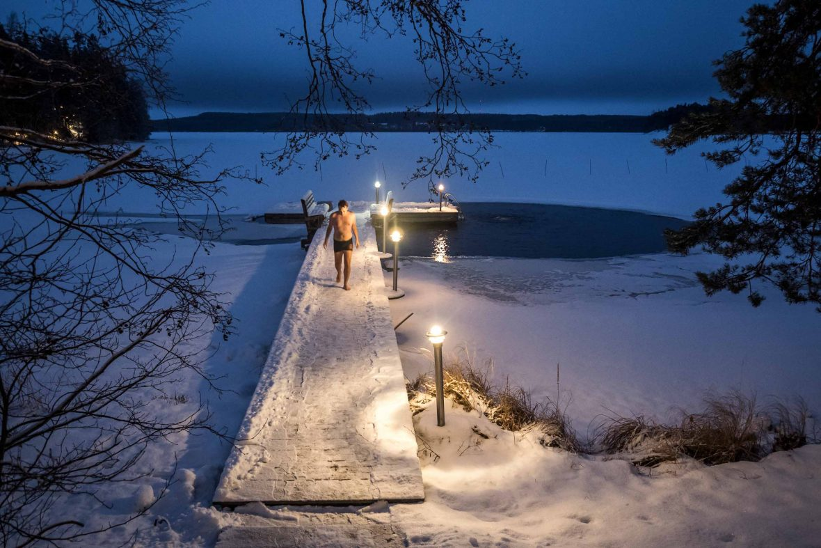 A man exits an icy cold lake after an afternoon swim, a popular activity in the cold, dark winter season.