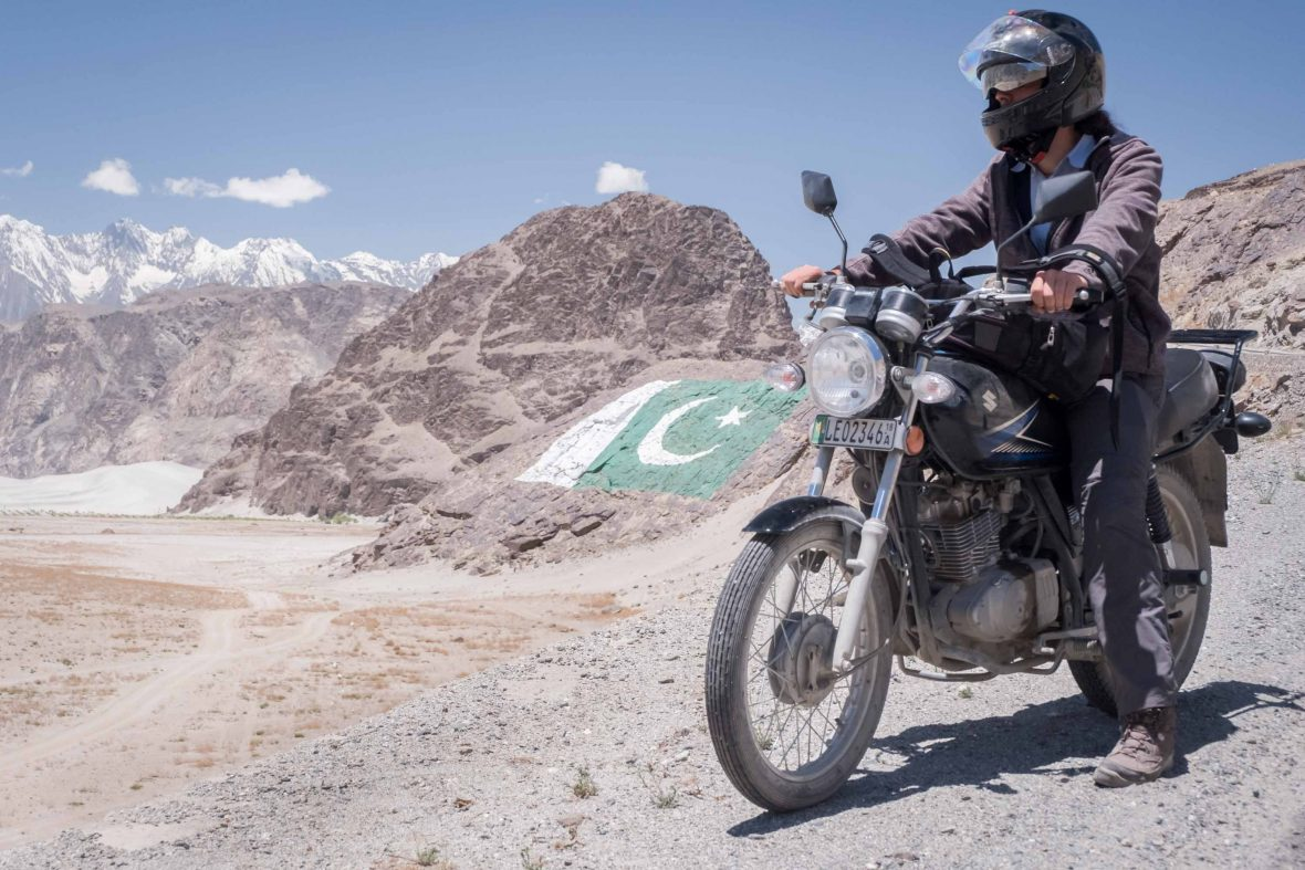 Pausing on the road beside a Pakistani flag in Gilgit-Baltistan, Pakistan, the main 200-kiometer link between the famous Karakoram Highway and Skardu.