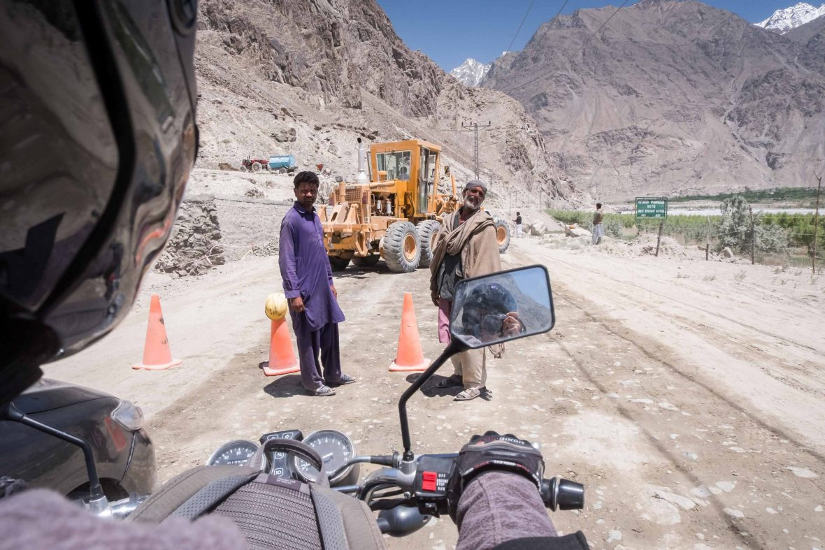 Road workers look up at the motorcyclist in Gilgit-Baltistan, Pakistan, the main 200-kilometer link between the Karakoram Highway and Skardu.