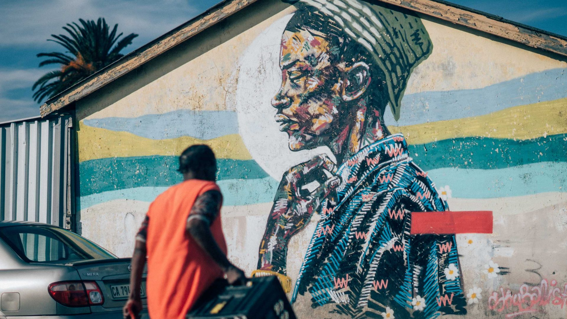 A local woman walks past by a Skubalisto mural in Langa, Cape Town.