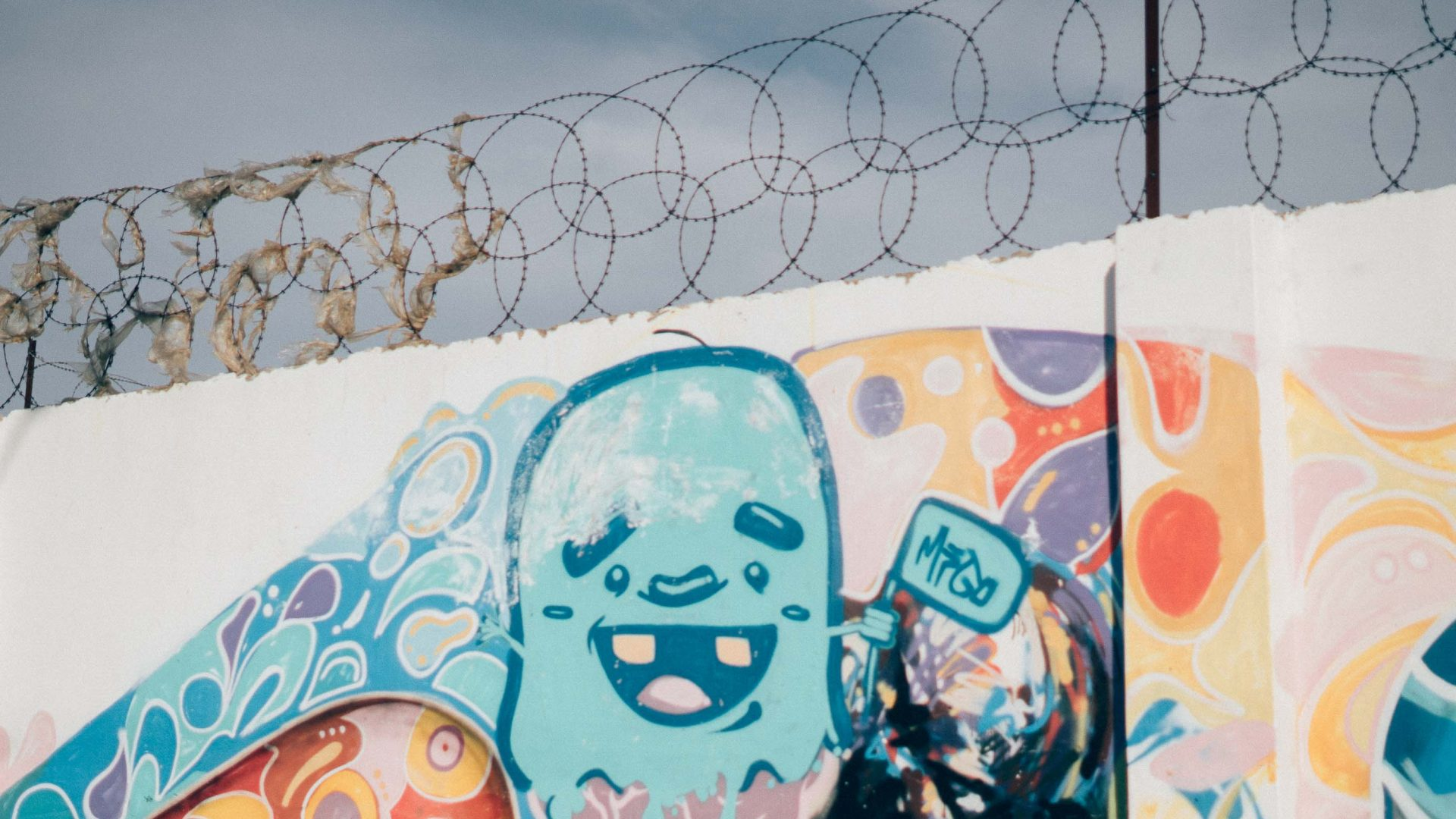 Graffiti adorns a barbed wire-protected wall in Langa, Cape Town.