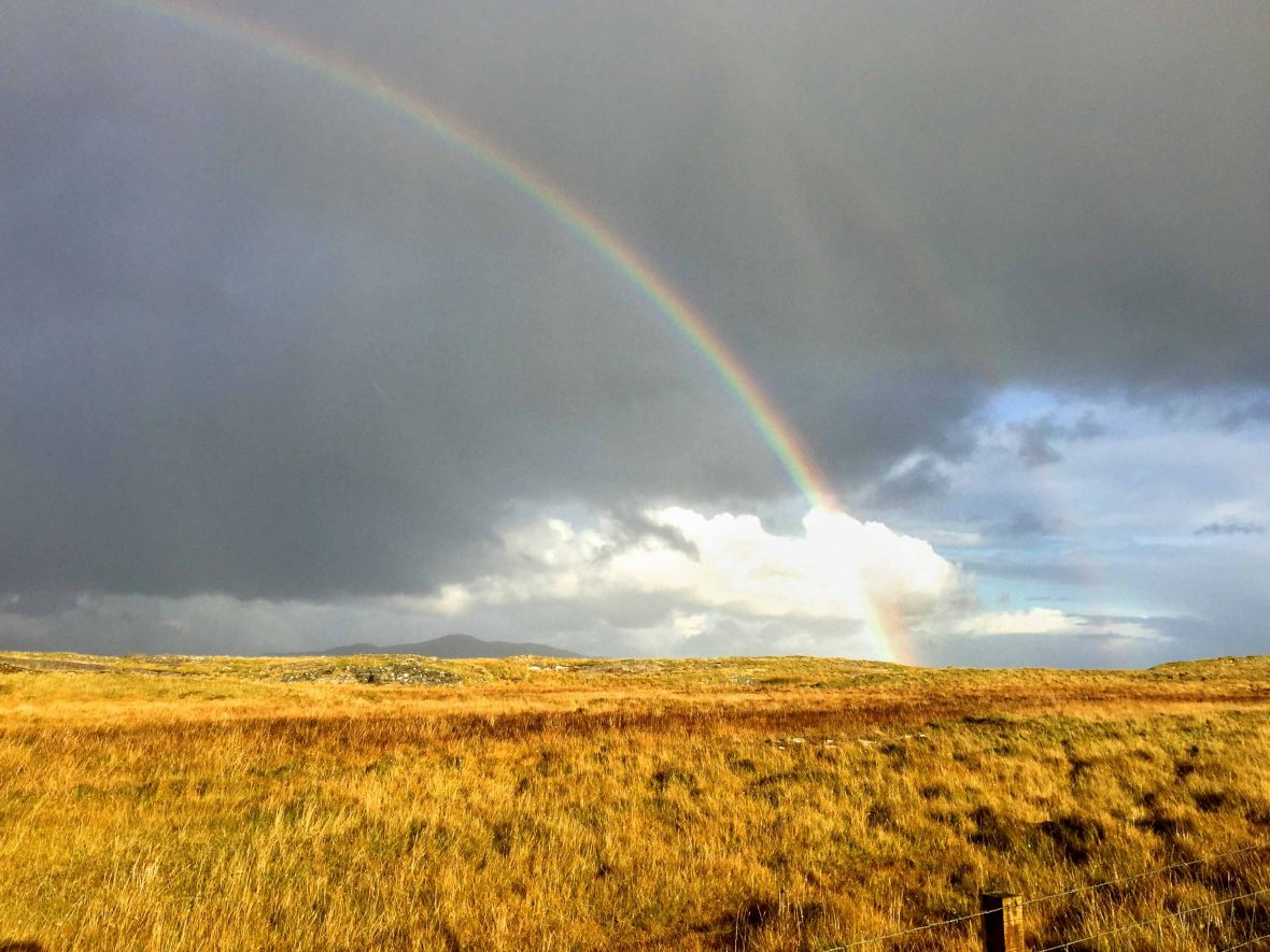 A rainbow appears above the sun-bathed fields of the Hebrides, Scotland.