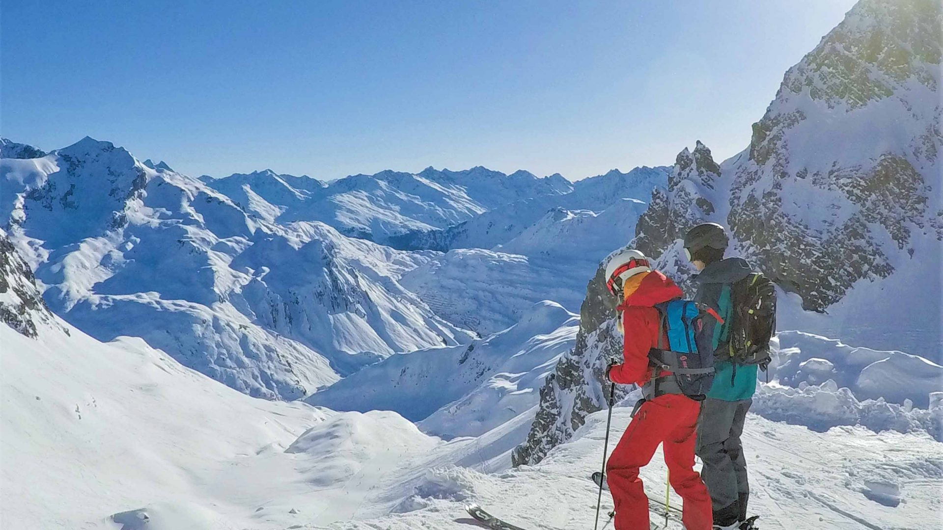 Two skiers stand at the edge of a mountain in St. Anton am Arlberg, Austria.