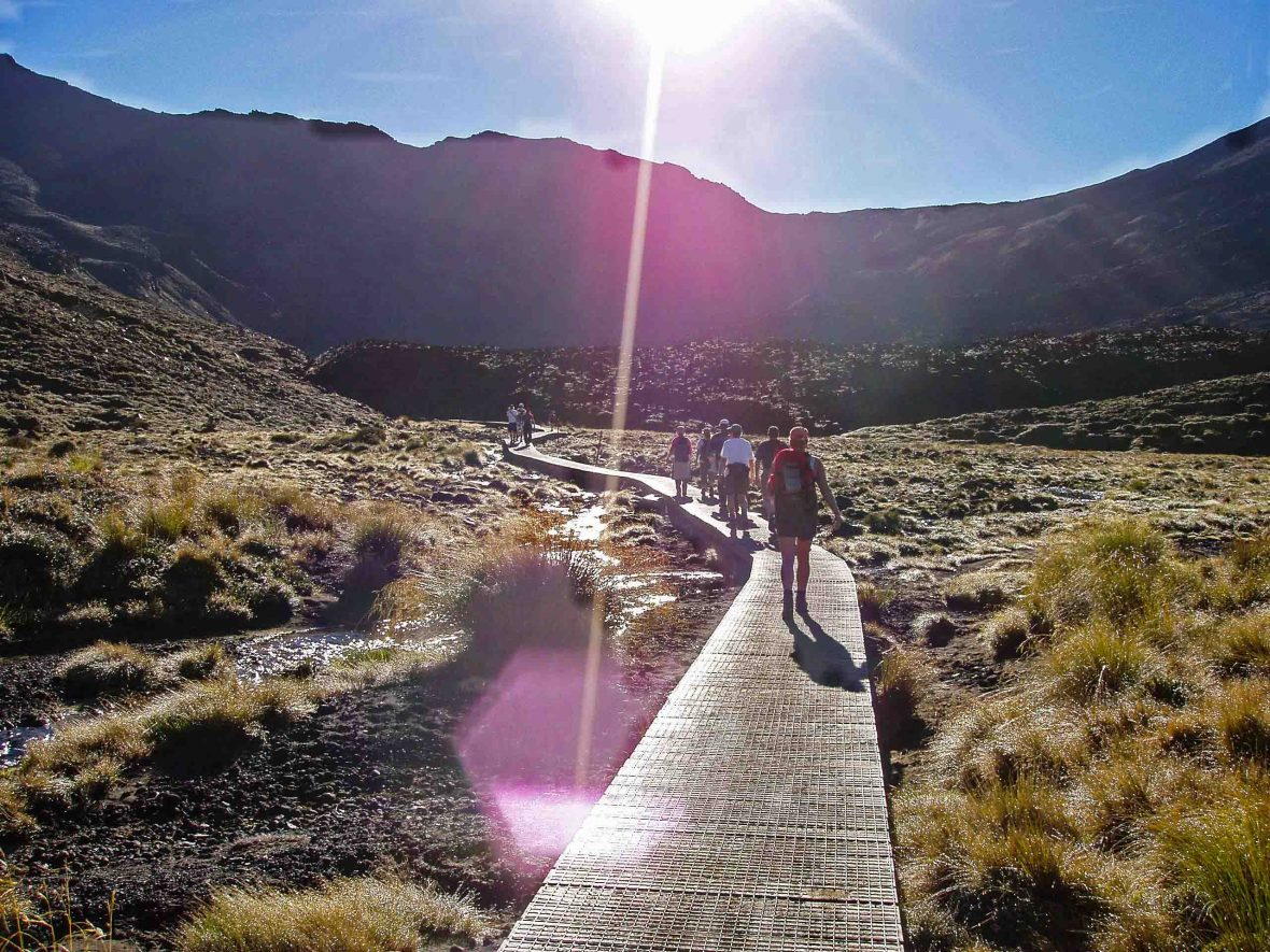 A boardwalk leads towards the blinding sun on the Tongariro Alpine Crossing, New Zealand.