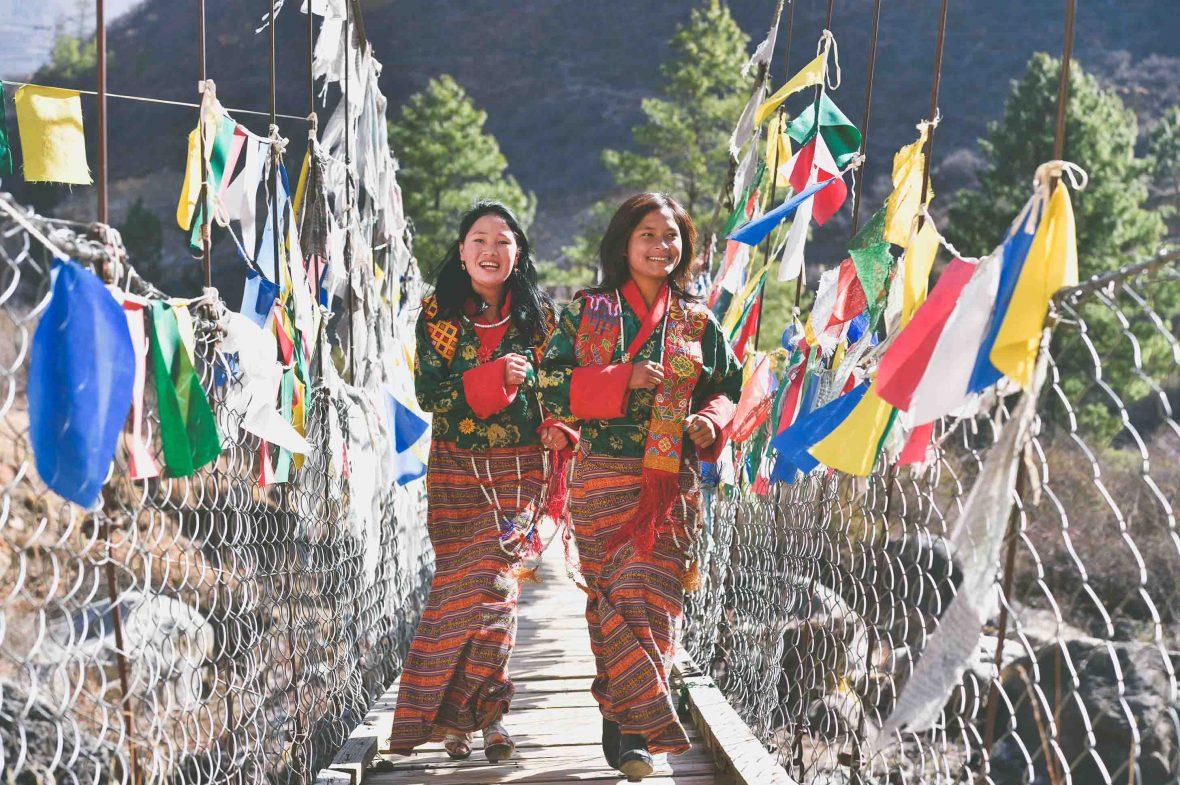 "Two women run across the foot bridge at Tachogang Lhakhang – meaning ""Temple of the Excellent Horse""."