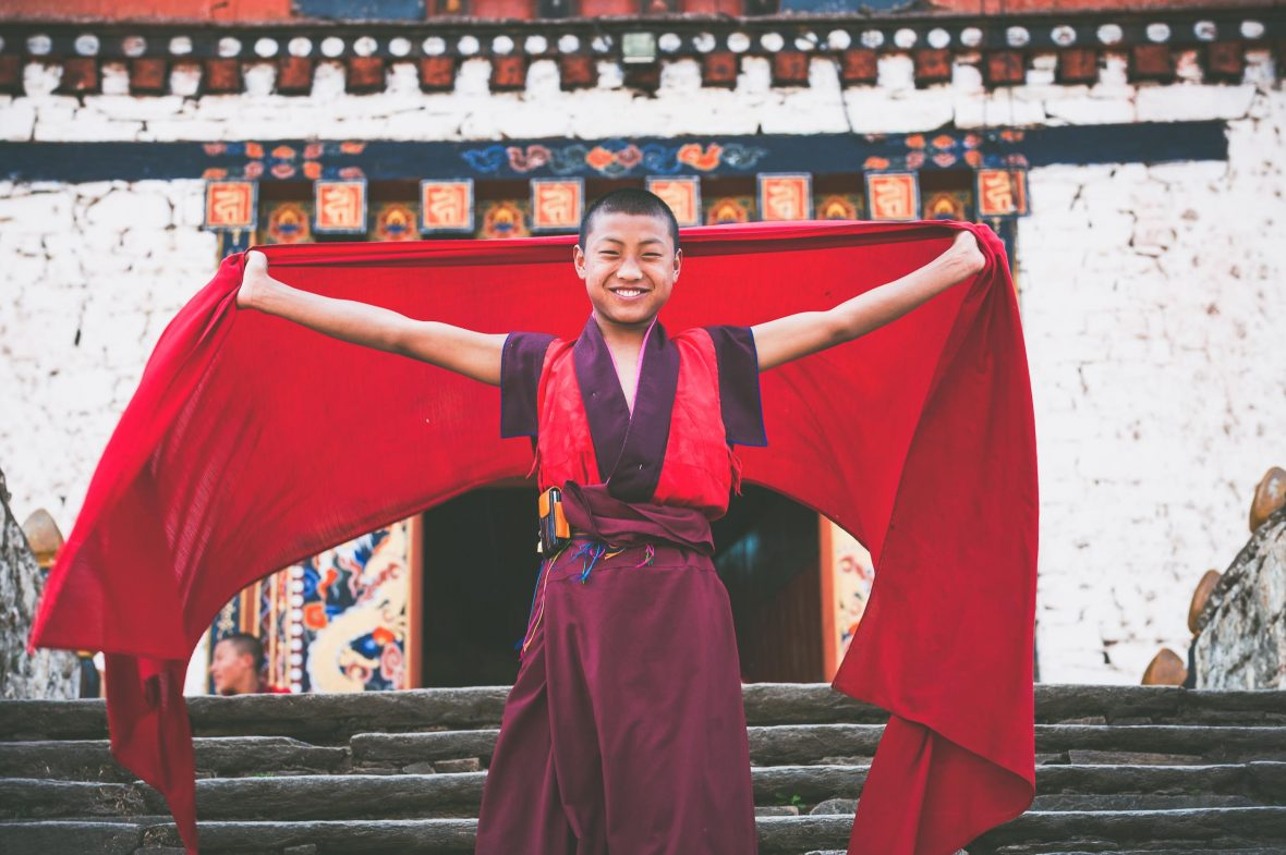 A young novice monk poses for the camera outside the main entrance to Paro's imposing 15th-century Rinpung Dzong fortress.