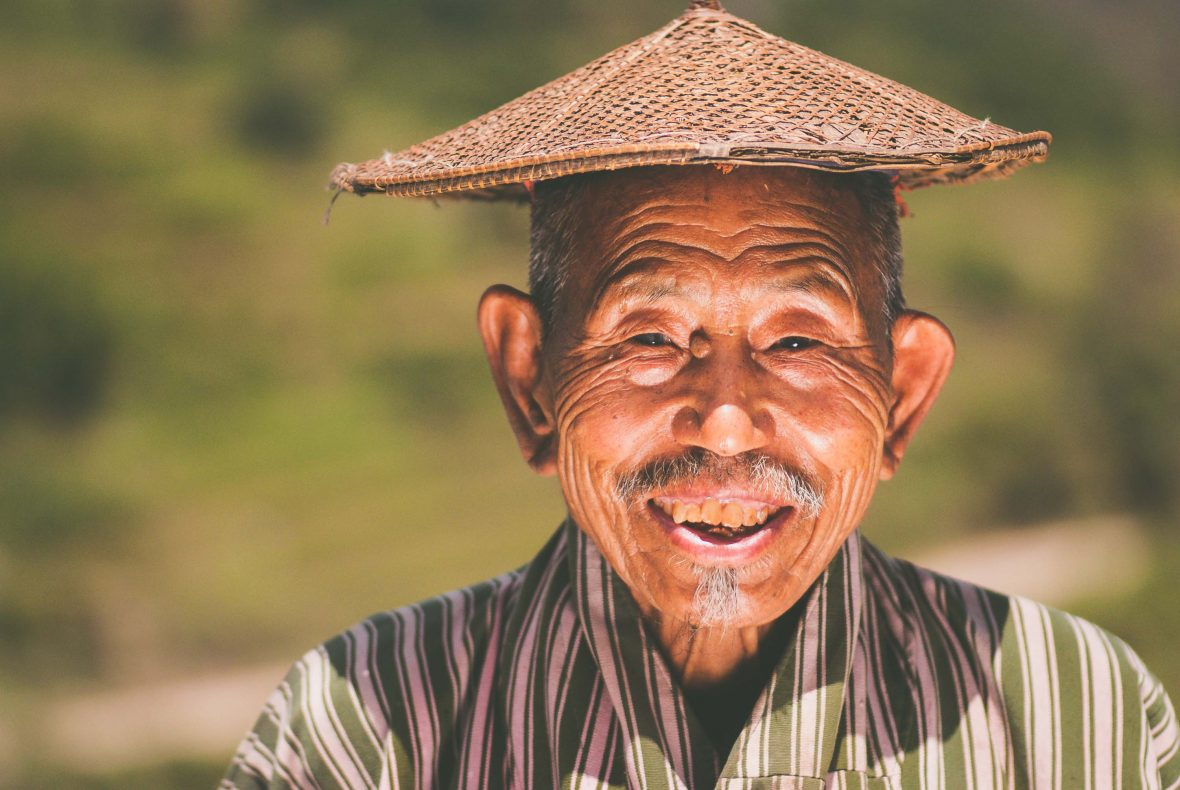 A man smiling in Bhutan where Gross National Happiness is measured.