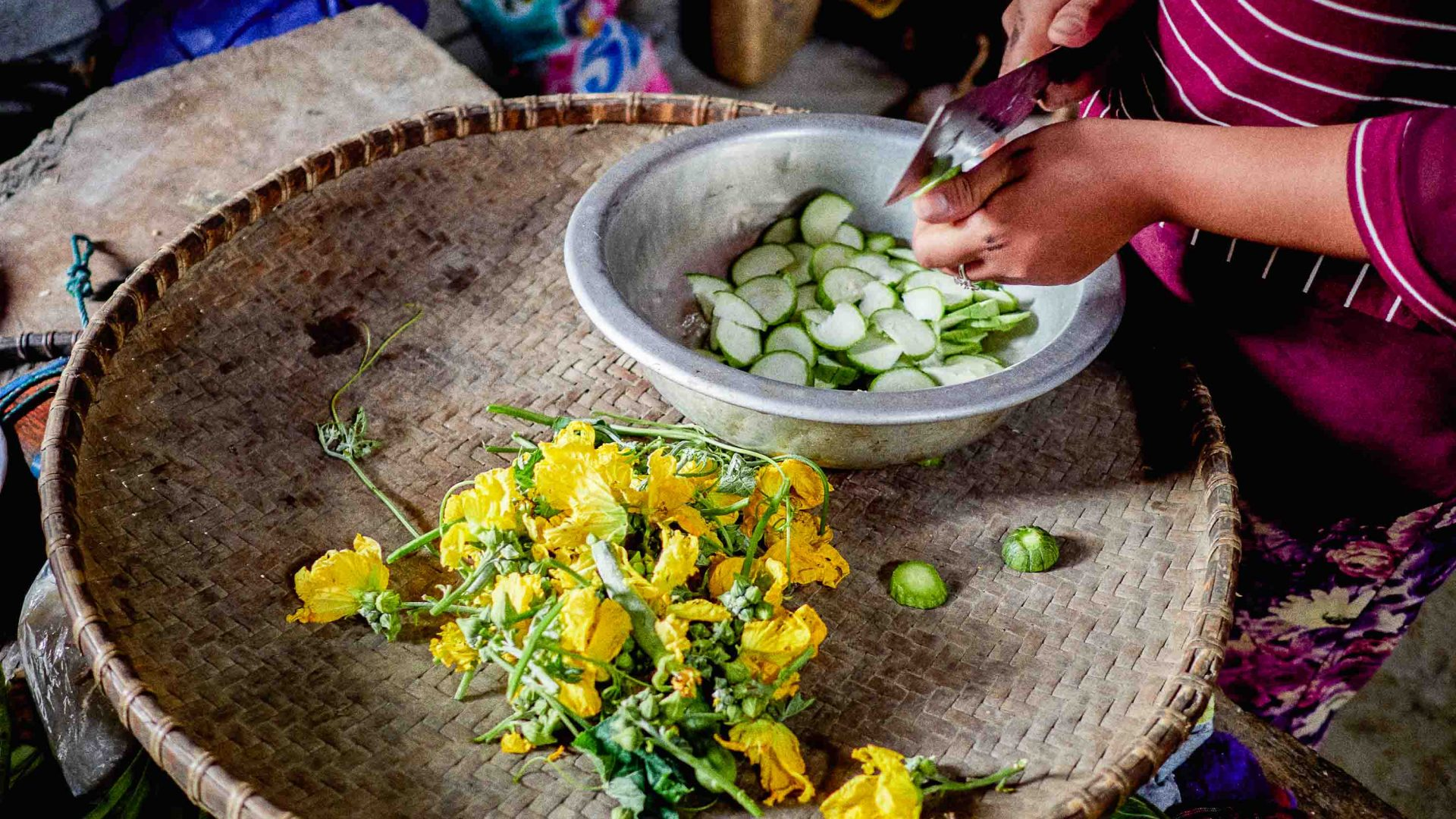 A woman prepares a meal using flowers and other greens in Laos.