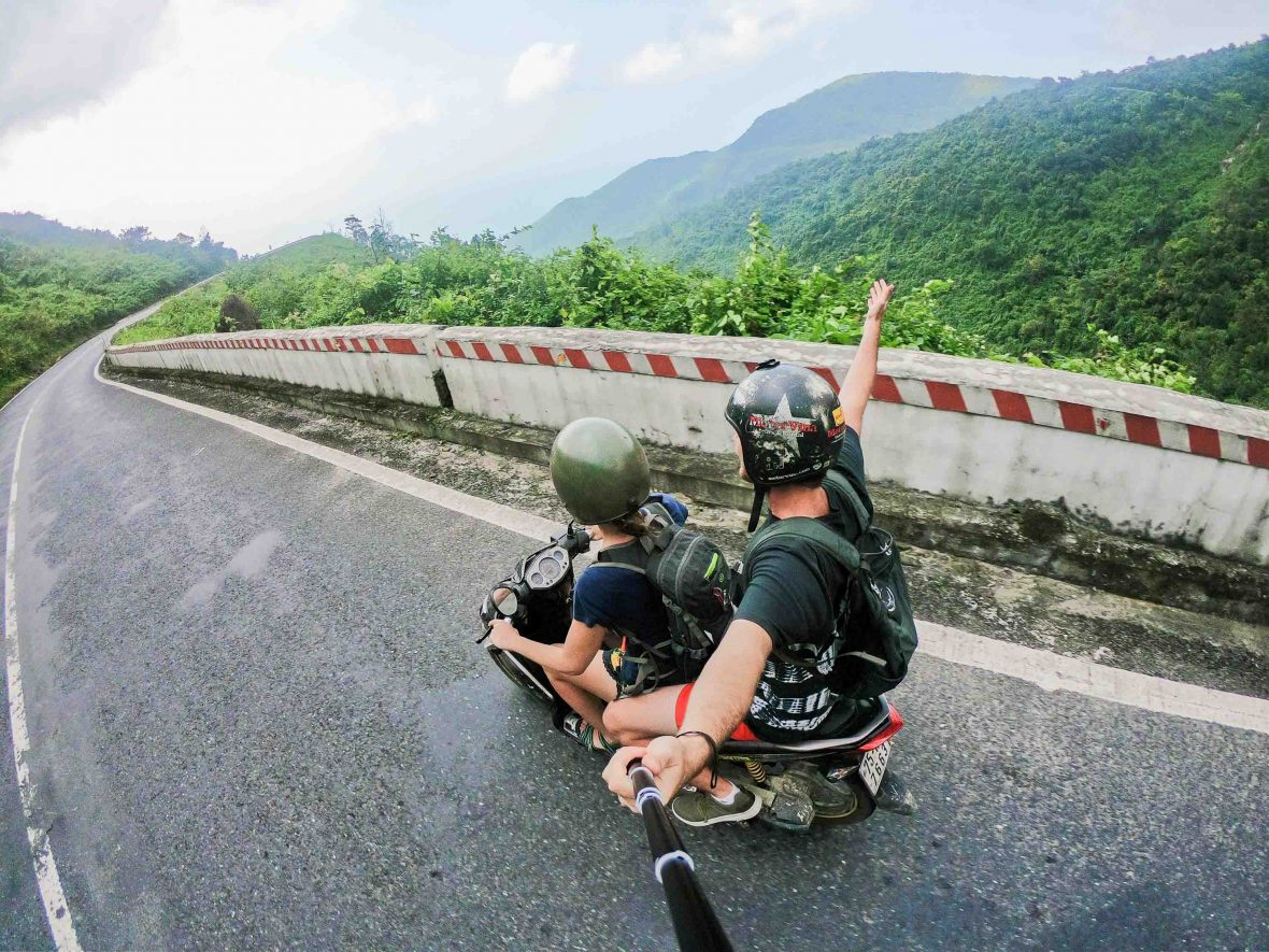 Travelers take a selfie while on a motorbike passing through Hai Van Pass in Vietnam.