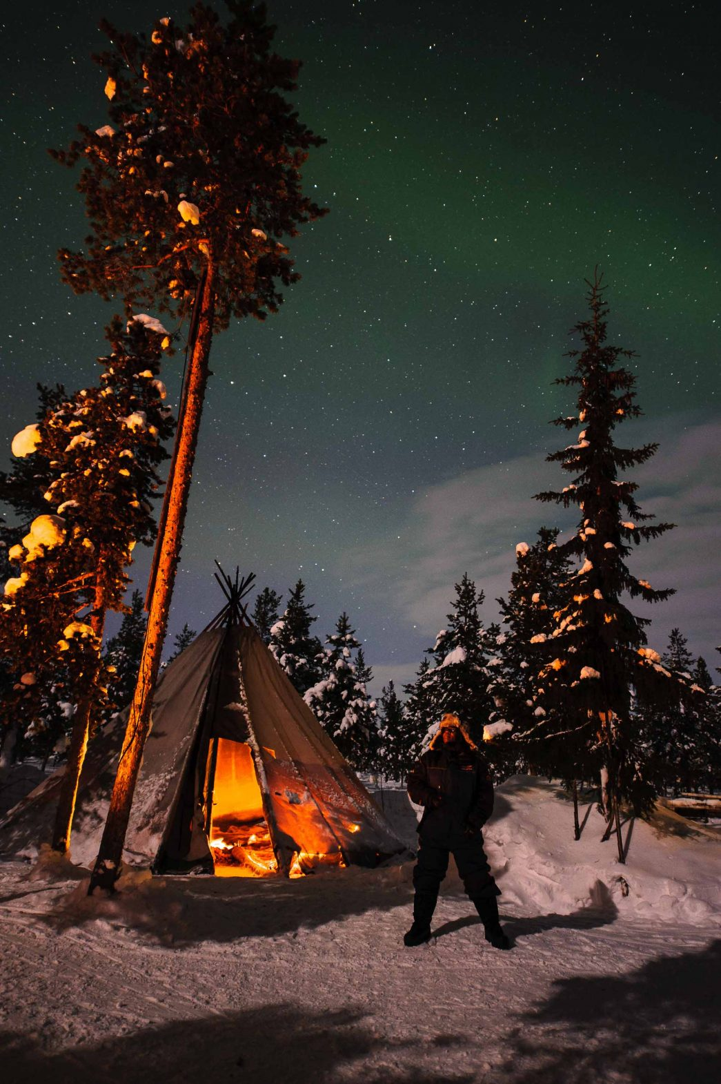 Lola looks up at the northern lights above tents at the reindeer lodge in Sweden.