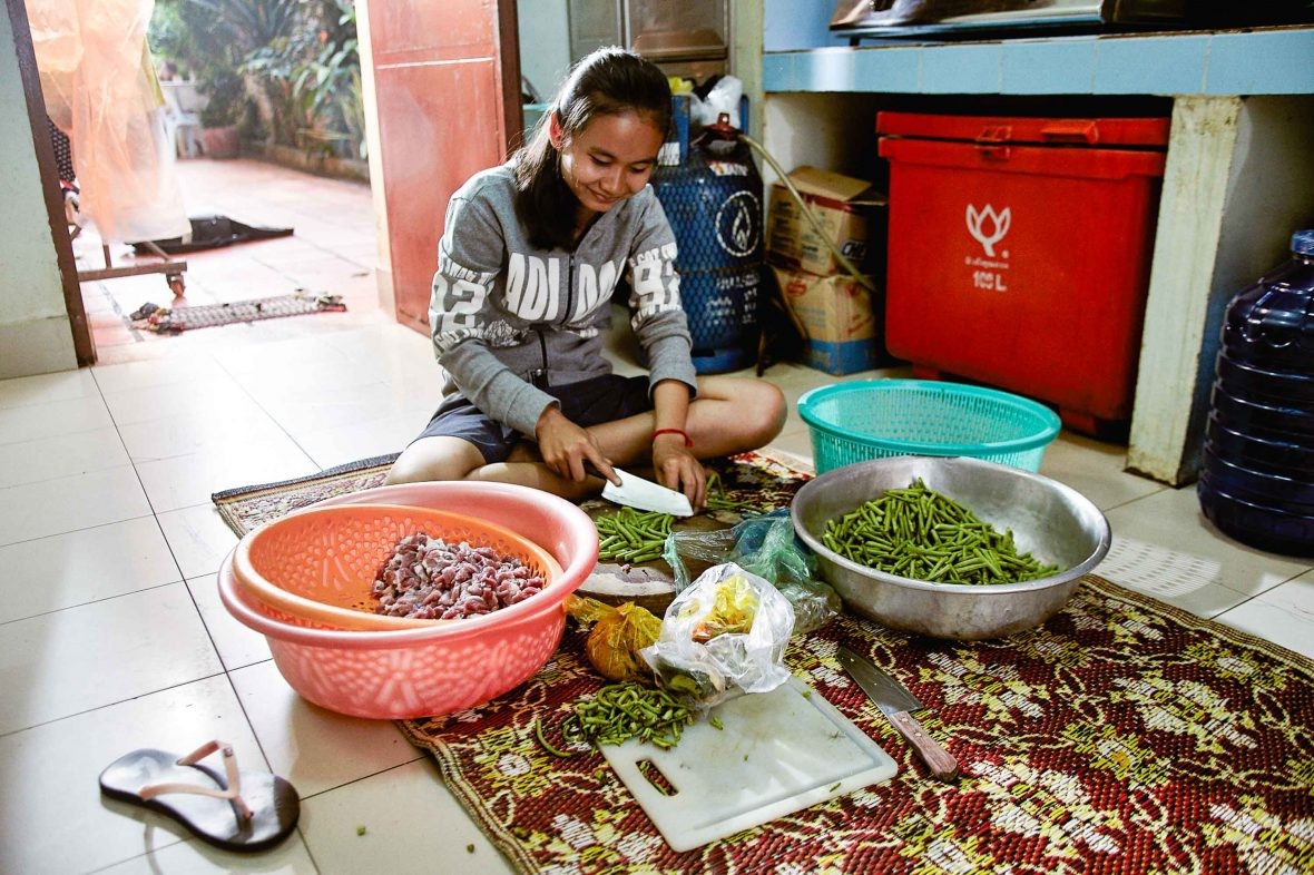 A woman prepares food on her floor in Cambodia.