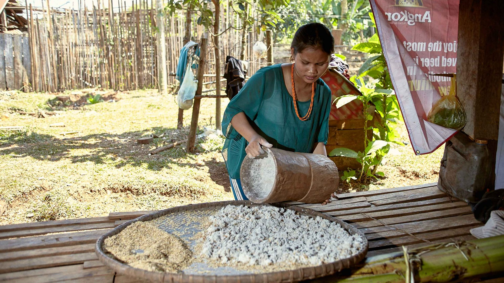 A woman pours out grains in Cambodia.