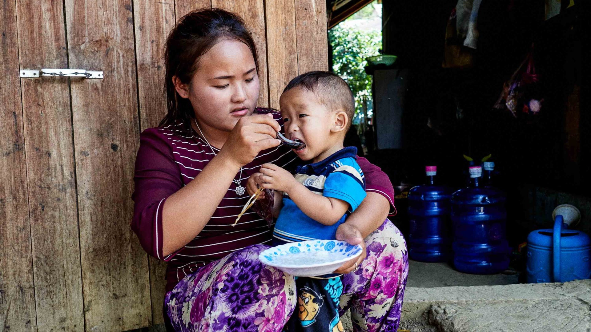 A mother feeds her child in Laos.