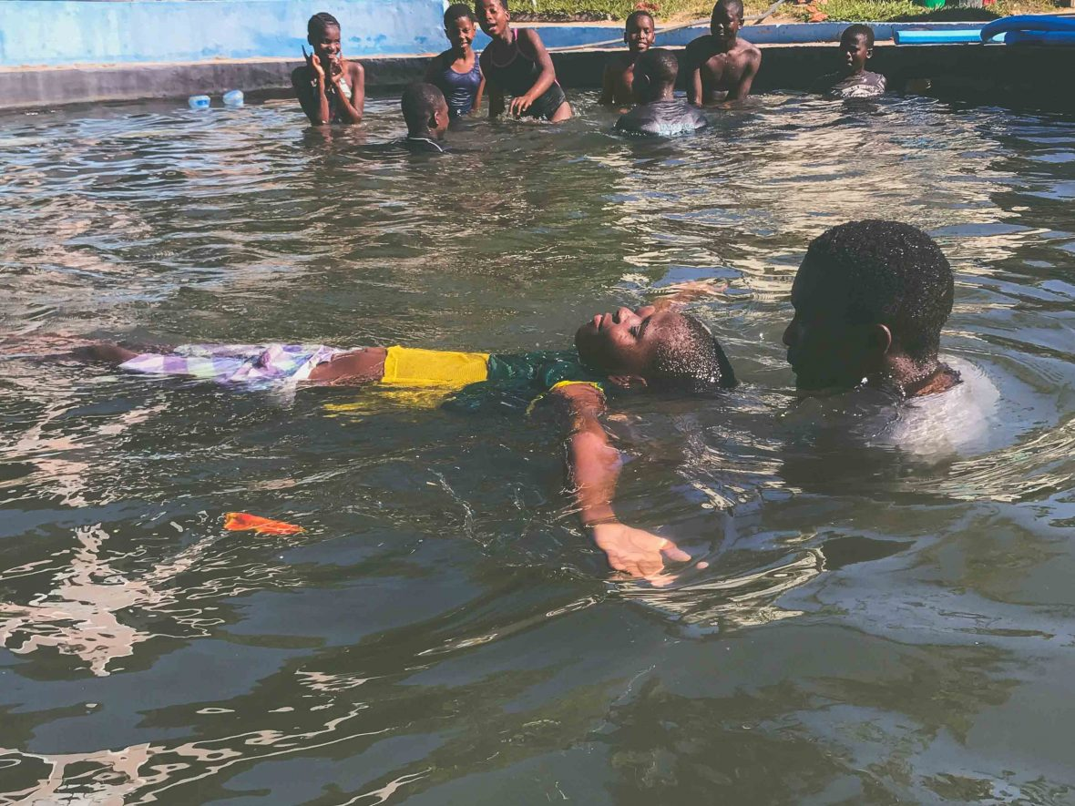 Local instructor Pedro teaches a child how to float in Tofo in southeastern Mozambique as part of the Ocean Guardians program.