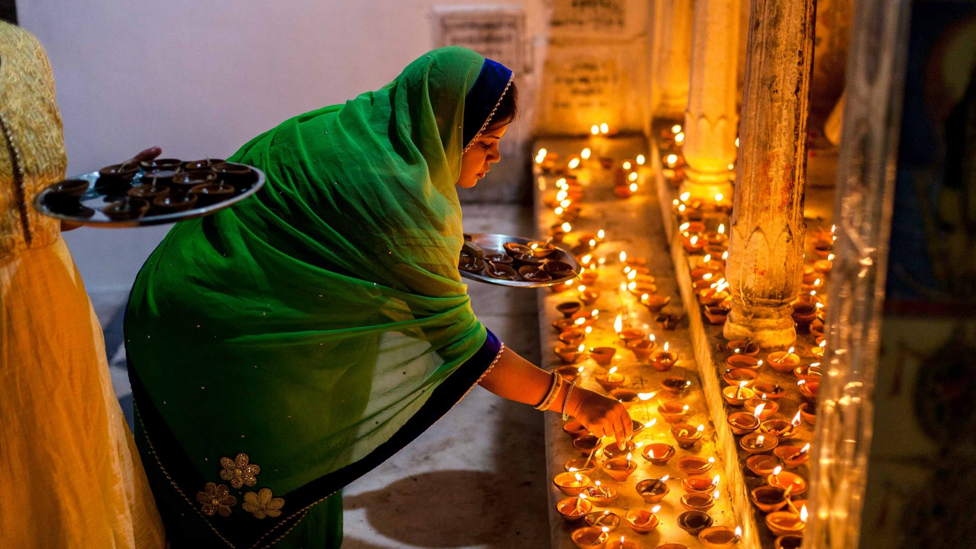 A woman lights candles on the ghats of Pushkar Lake.