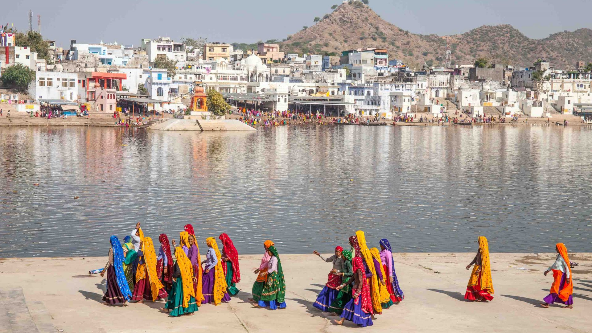 Rajasthani women walk along the banks of Pushkar Lake, with Pushkar town in the background.