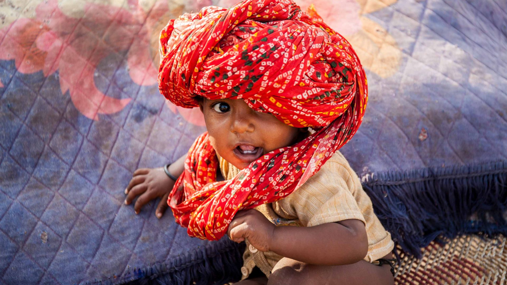 A baby wears his father's turban in a camp of herder families during Pushkar Camel Fair.