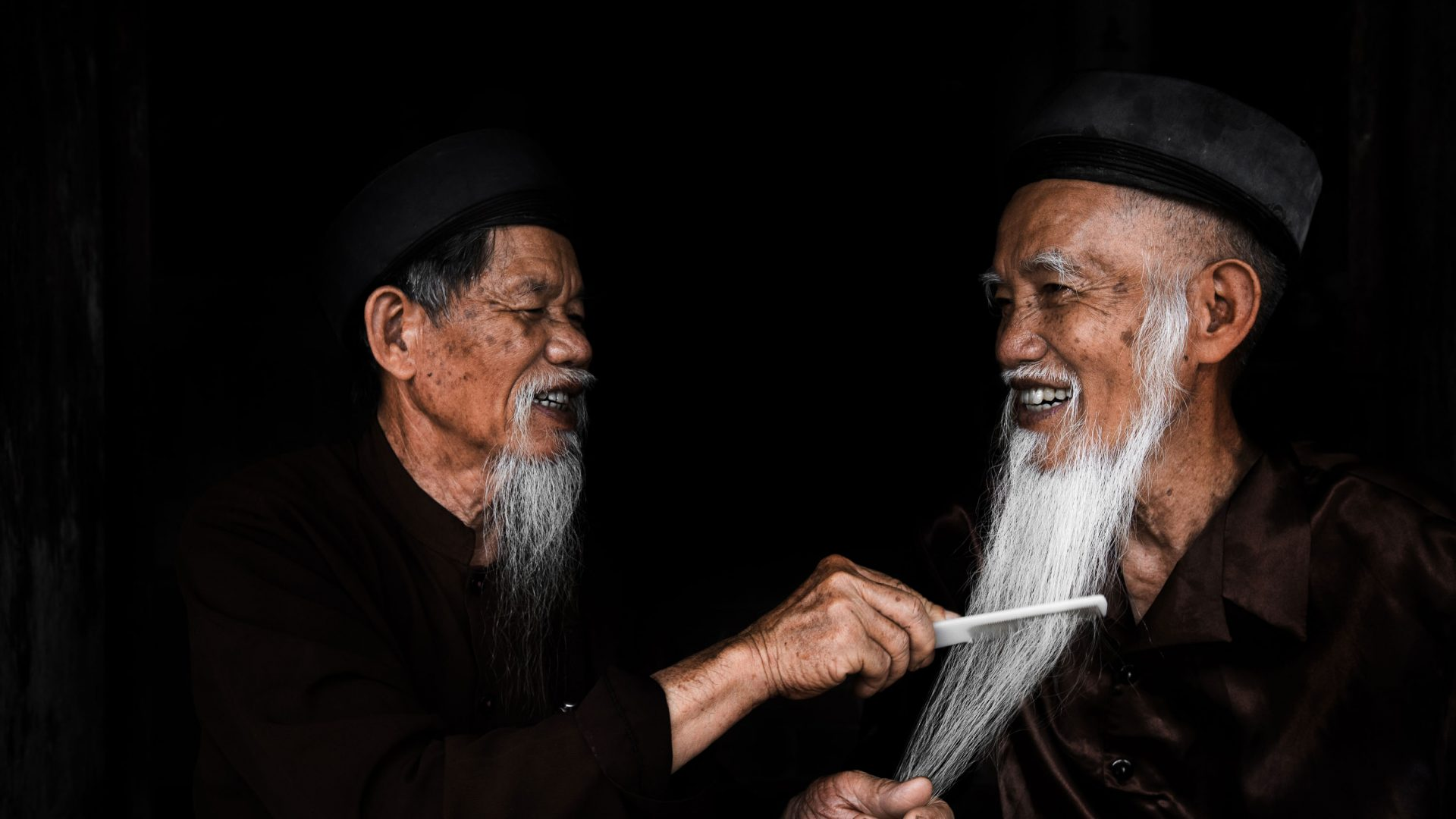 Two men brush each other's beards in Vietnam.
