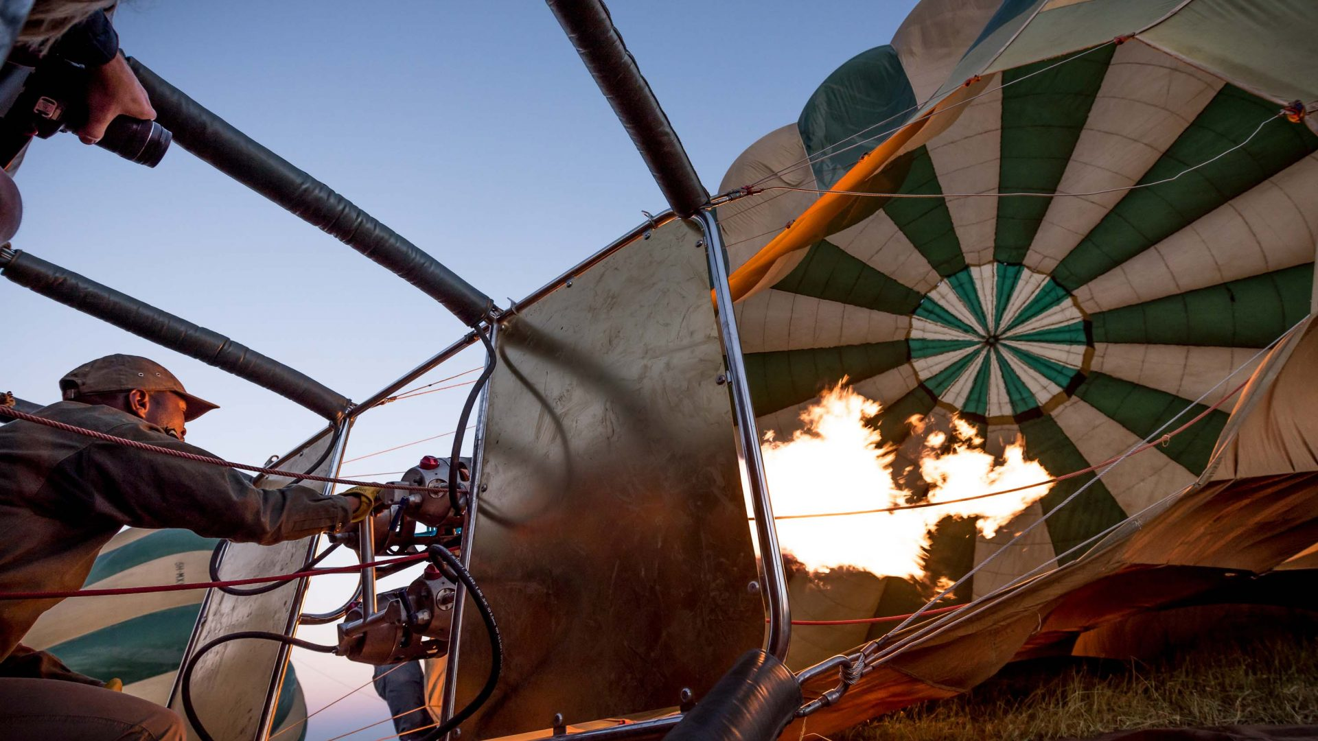 A hot air balloon is filled with gas, ready to rise above the Serengeti, Tanzania.