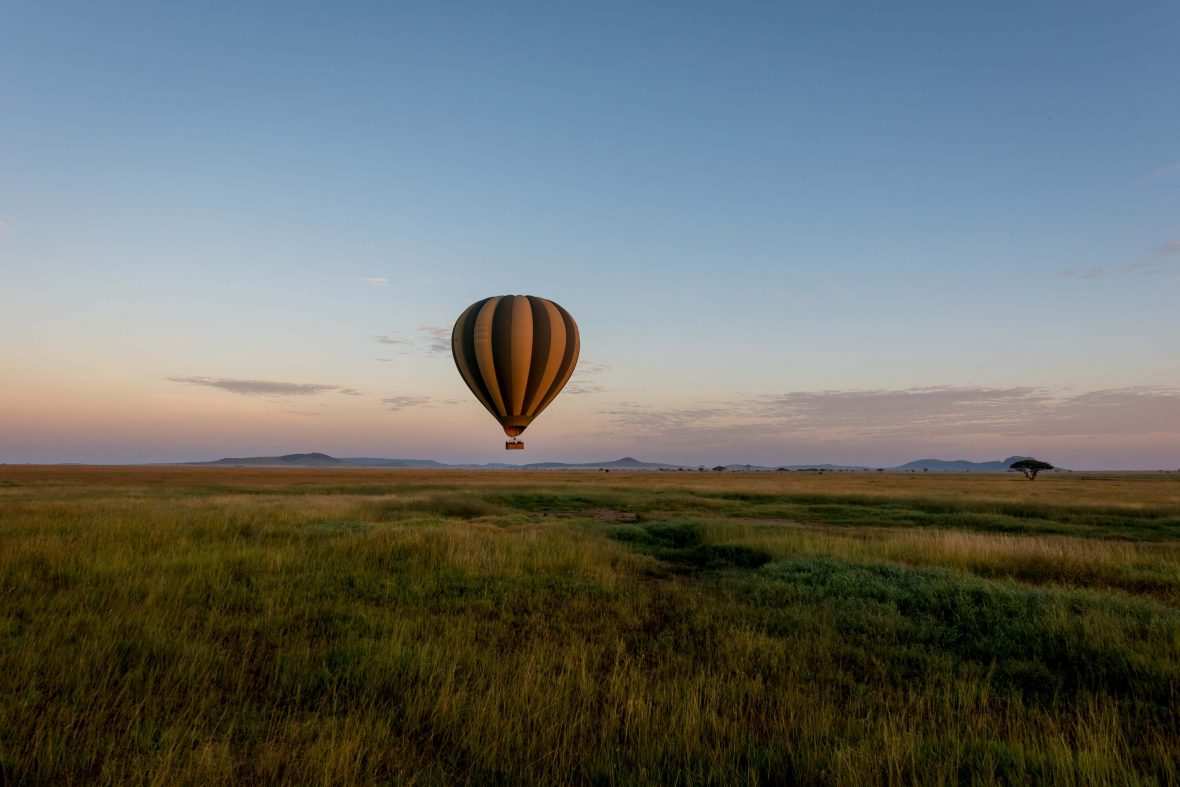 A hot air balloon in the warm light of dawn, moves slowly over the Serengeti in Tanzania.