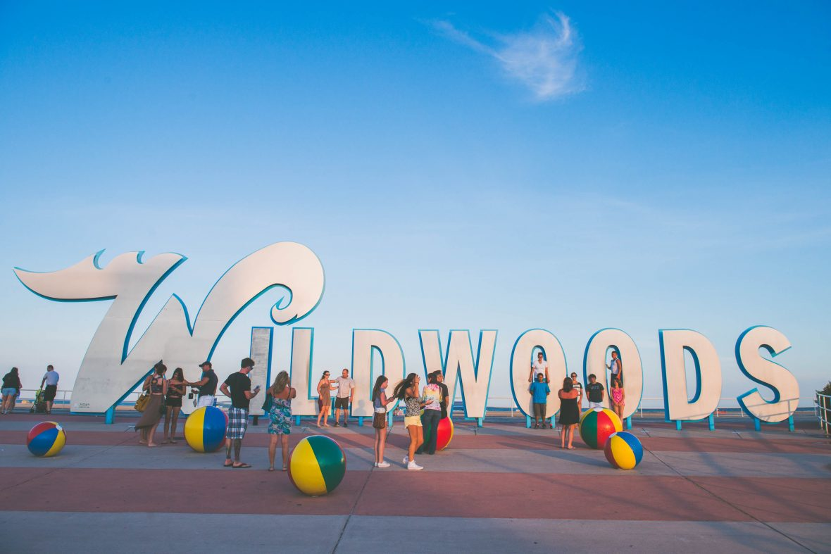 People mill around the Wildwoods sign at the end of the day.