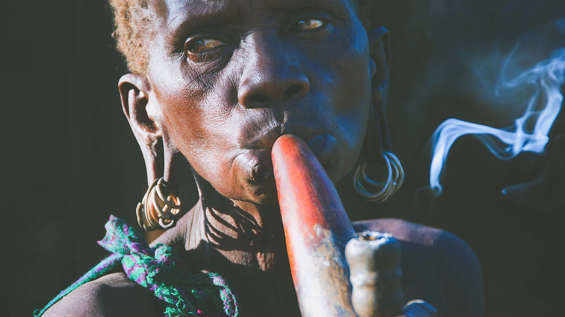 A woman smokes a calibash pipe in Ethiopia.