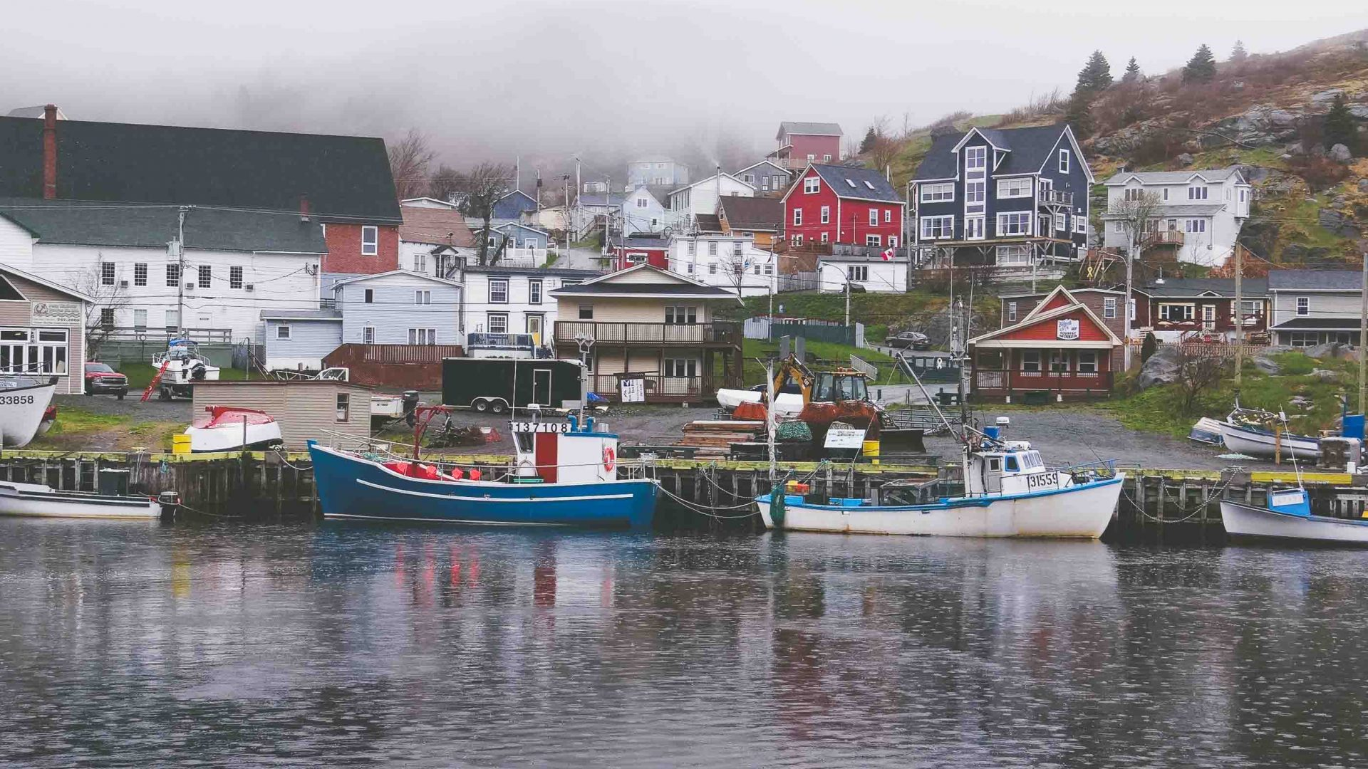 Colorful fishermen's houses appear from the fog in Petty Harbor, Newfoundland.
