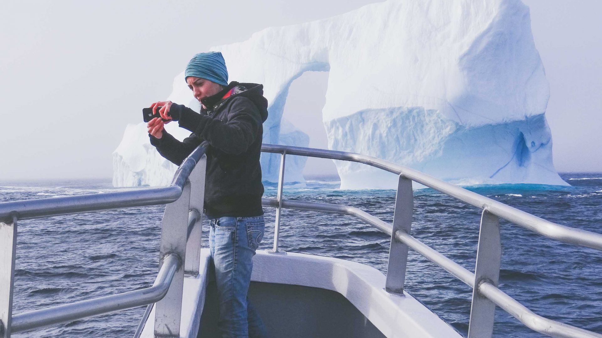 A tourist takes a selfie with an iceberg on board the Iceberg Quest.