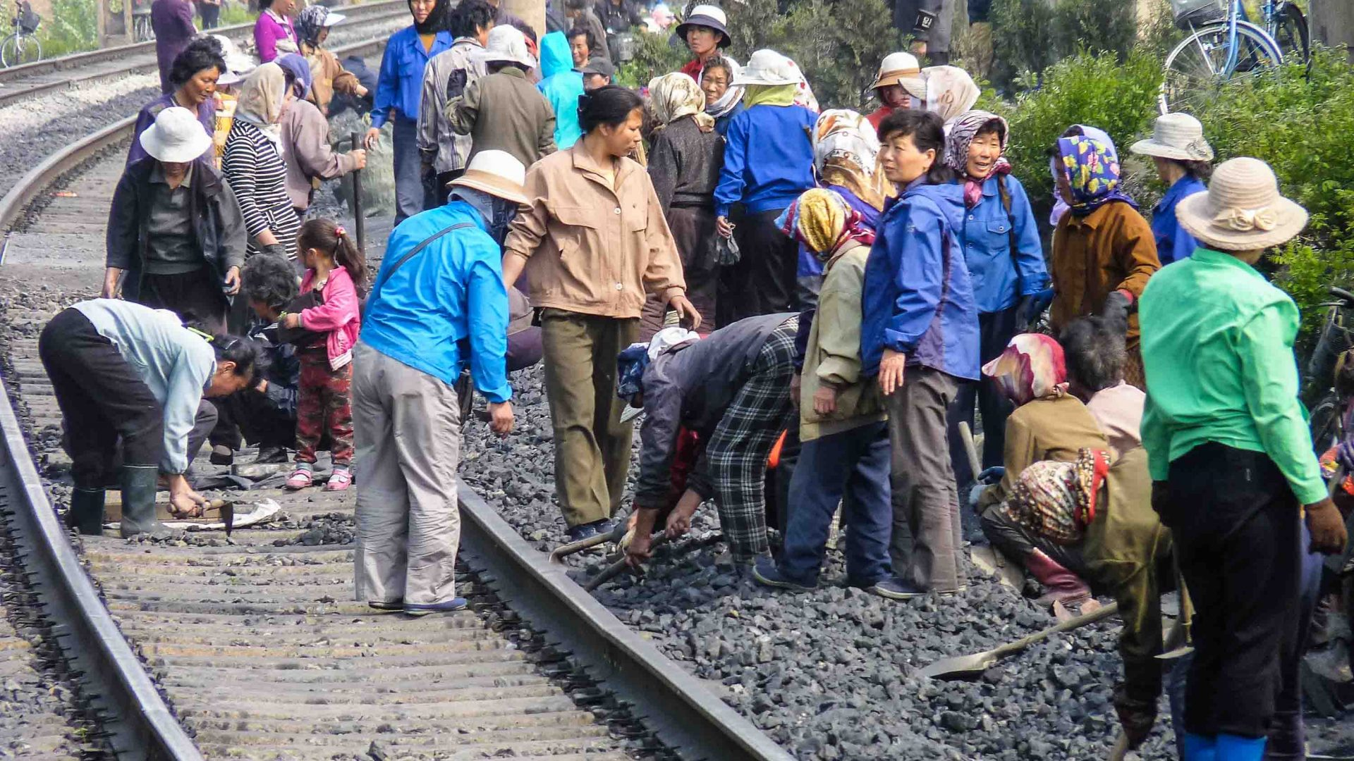 Train workers work by hand on the rail lines.