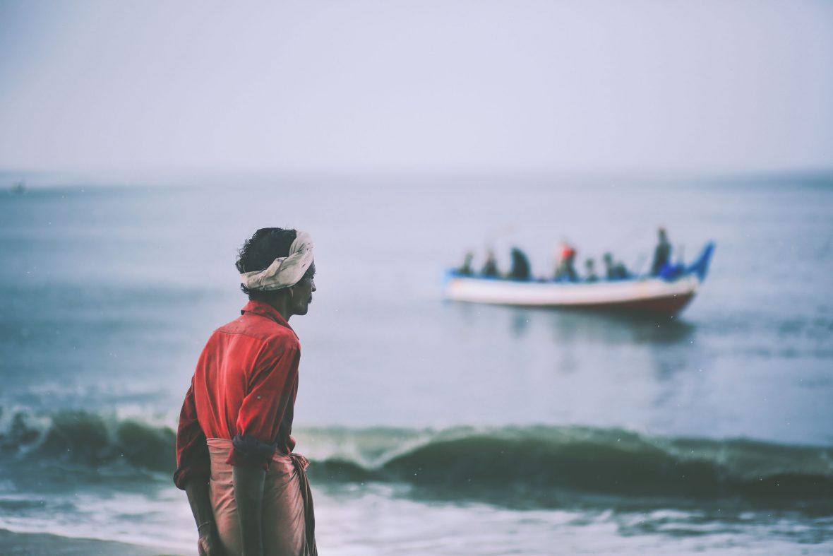 A man looks out at a Marari Beach fish landing, Kerala.