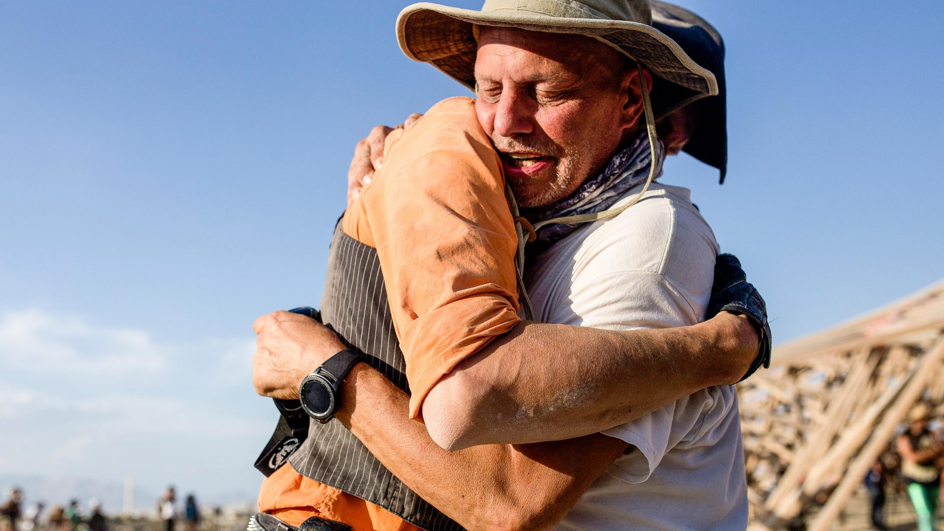 Burning Wish founder Aaron 'Slim' Muszalski hugs Bryan Monahan outside of the temple after the Survivors Walk at Burning Man.